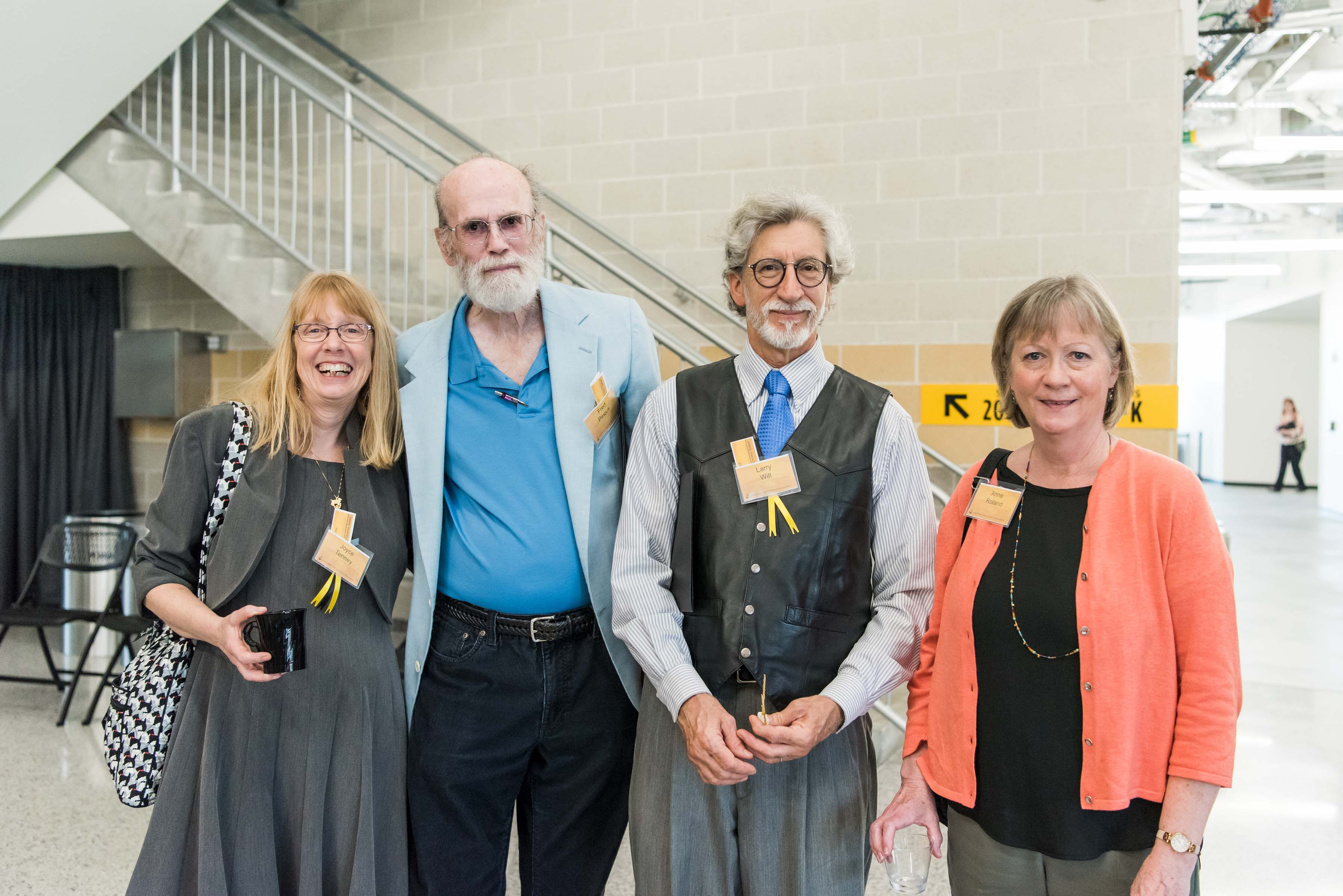 Group of four pose together in Event center at Wisdom Institute lunch