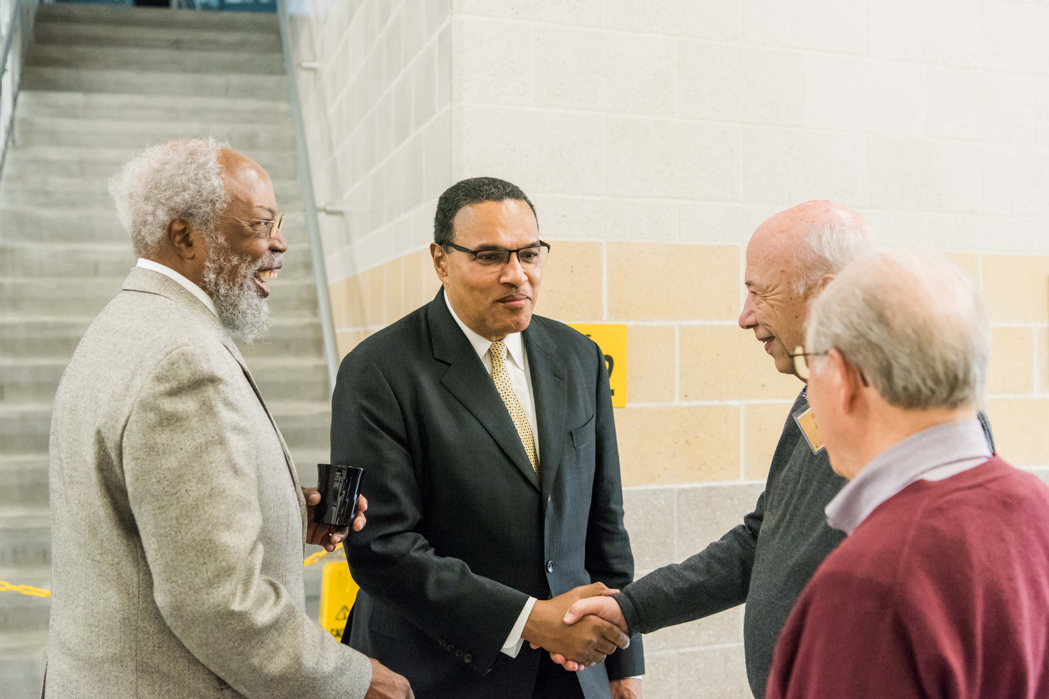 Hrabowski shakes hands with people at Wisdom Institute lunch
