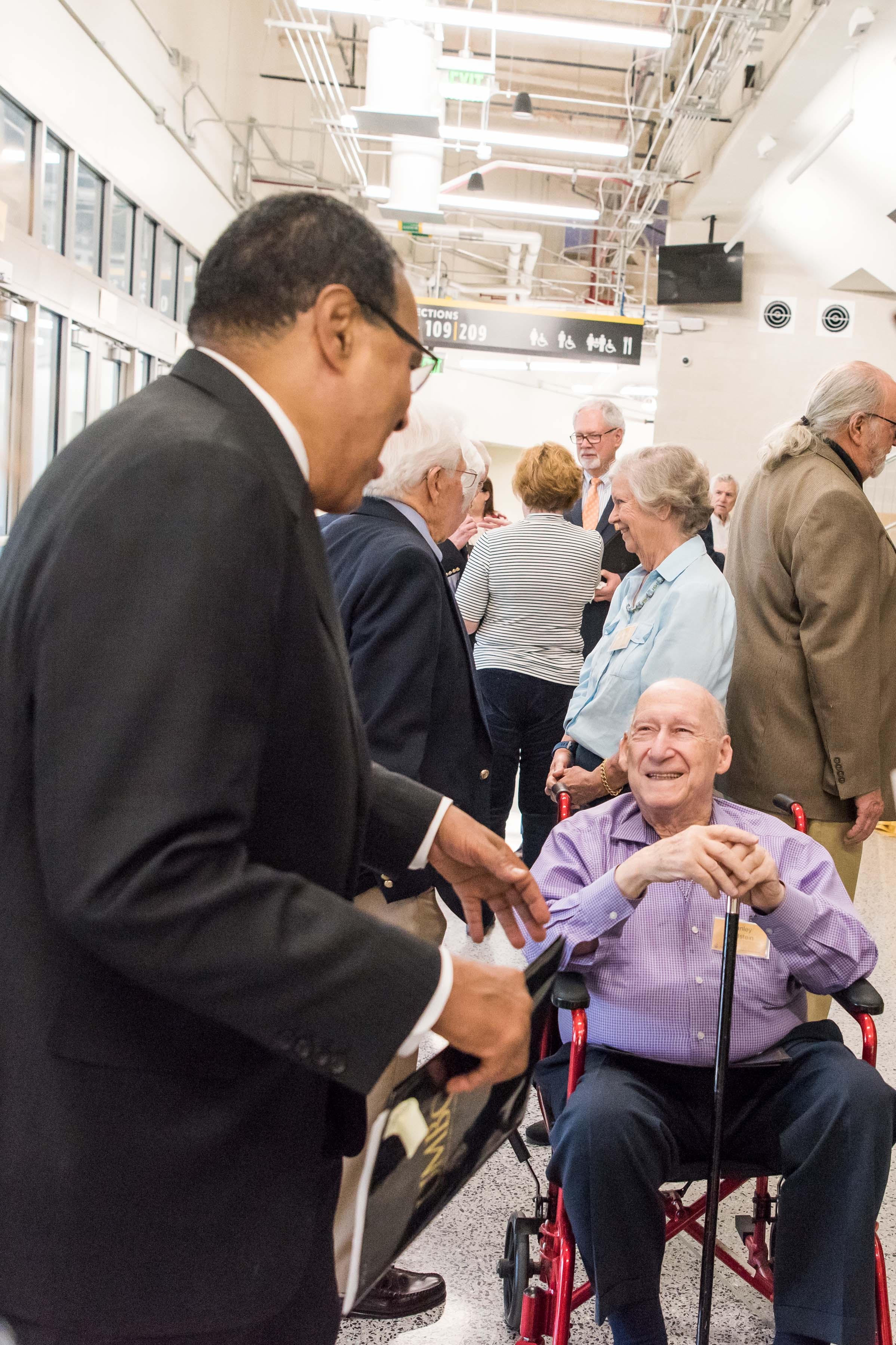Hrabowski leans down to talk to man in wheel chair at Wisdom Institute lunch