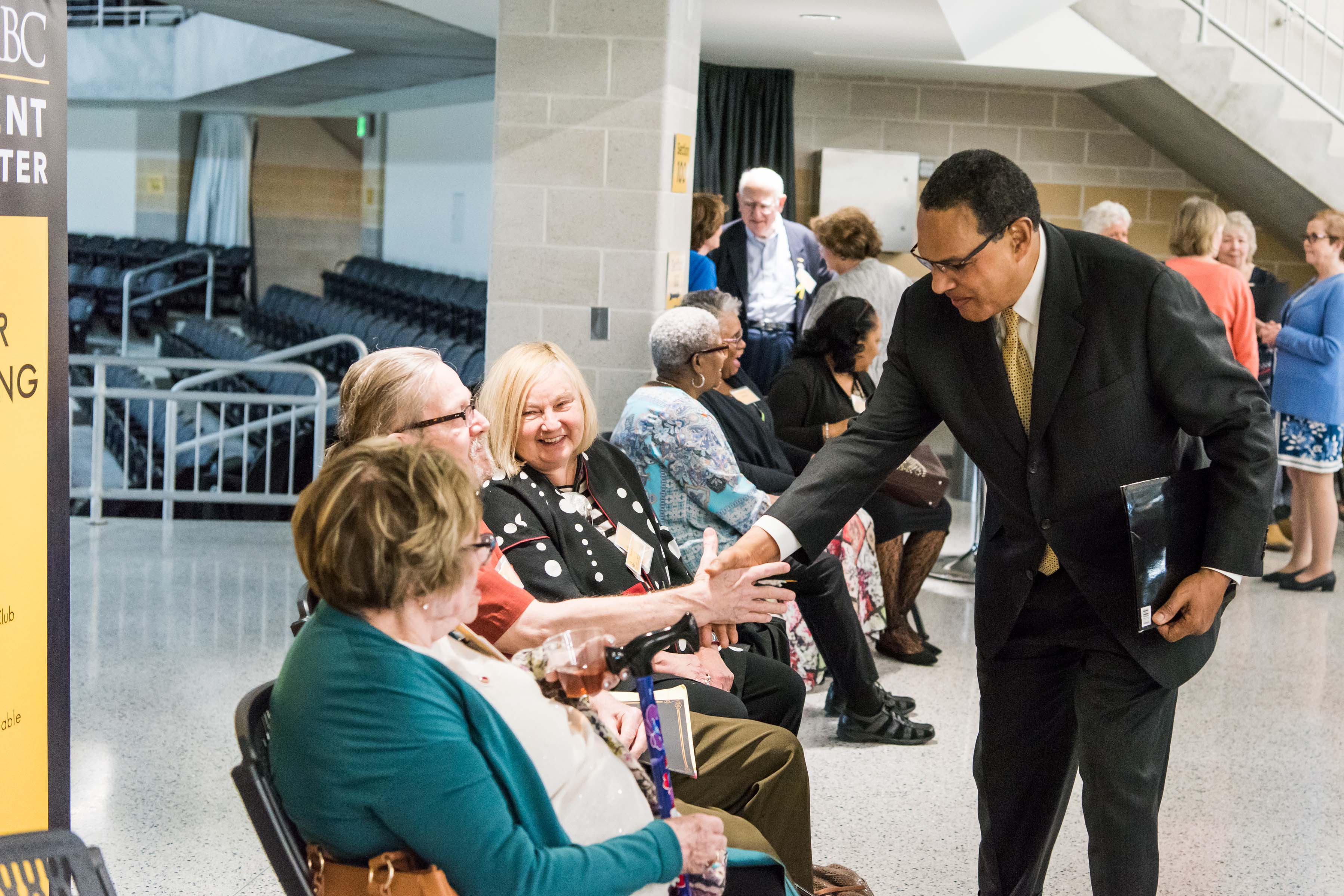 Hrabowski leans down to shake people's hands at Wisdom Institute lunch