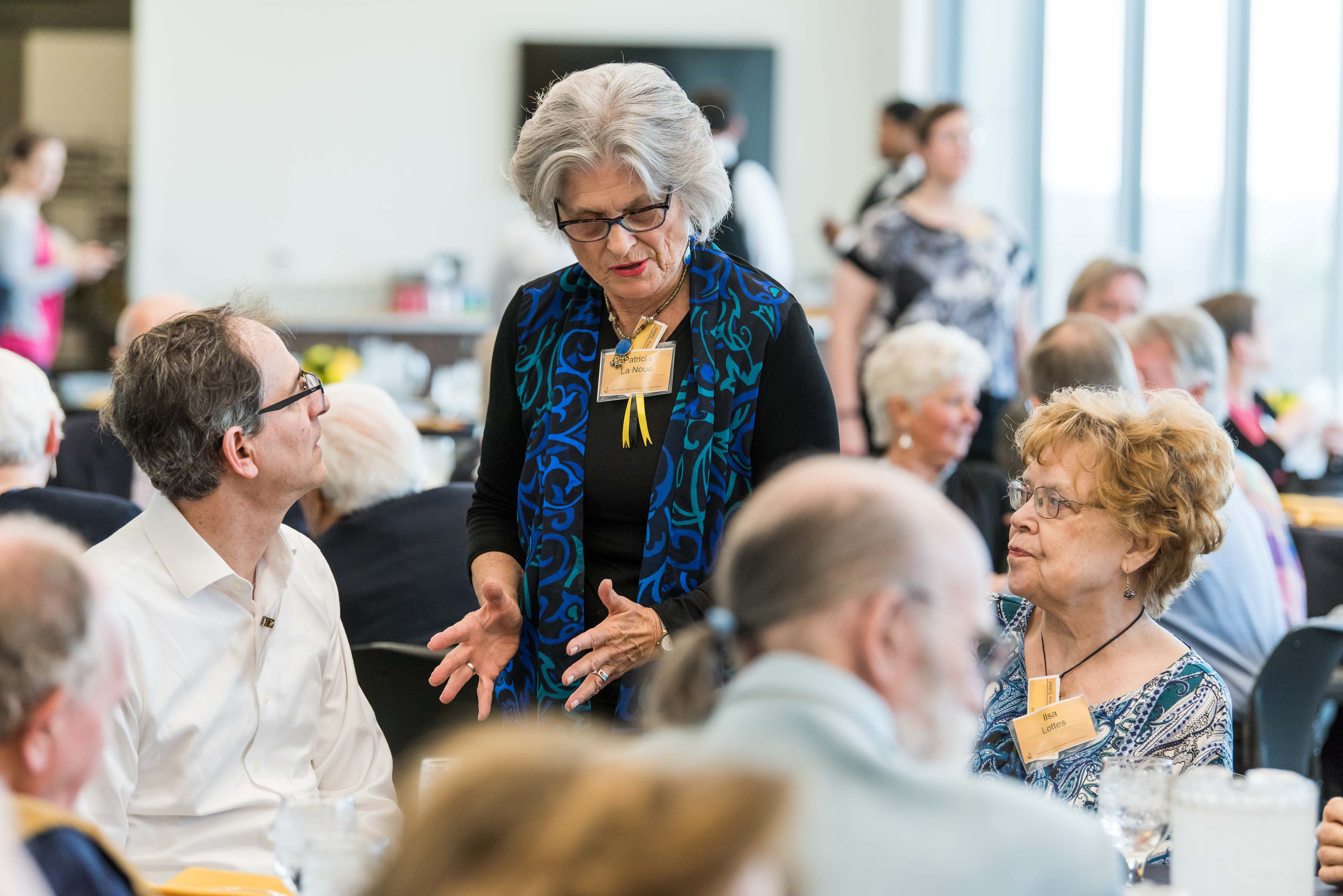 Woman approaches table talking, at Wisdom Institute lunch