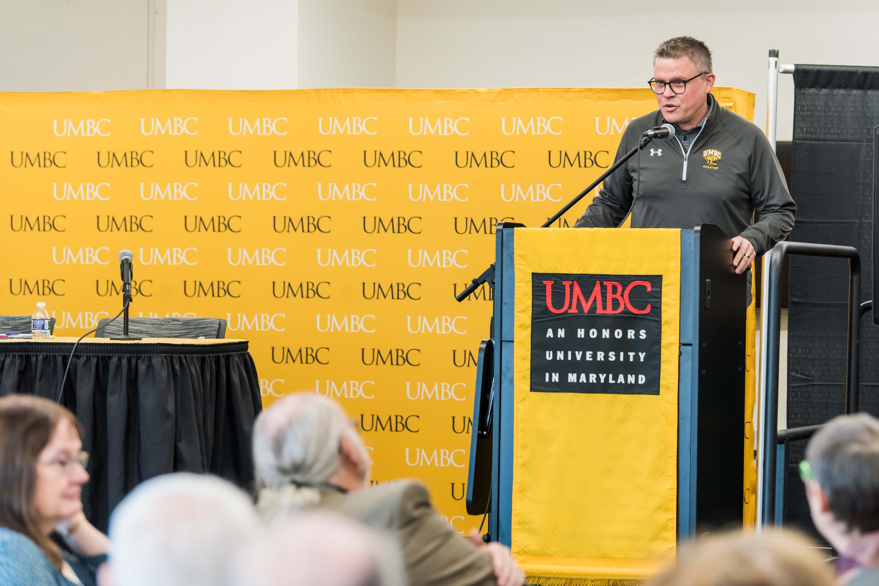 Man stands behind UMBC podium to talk