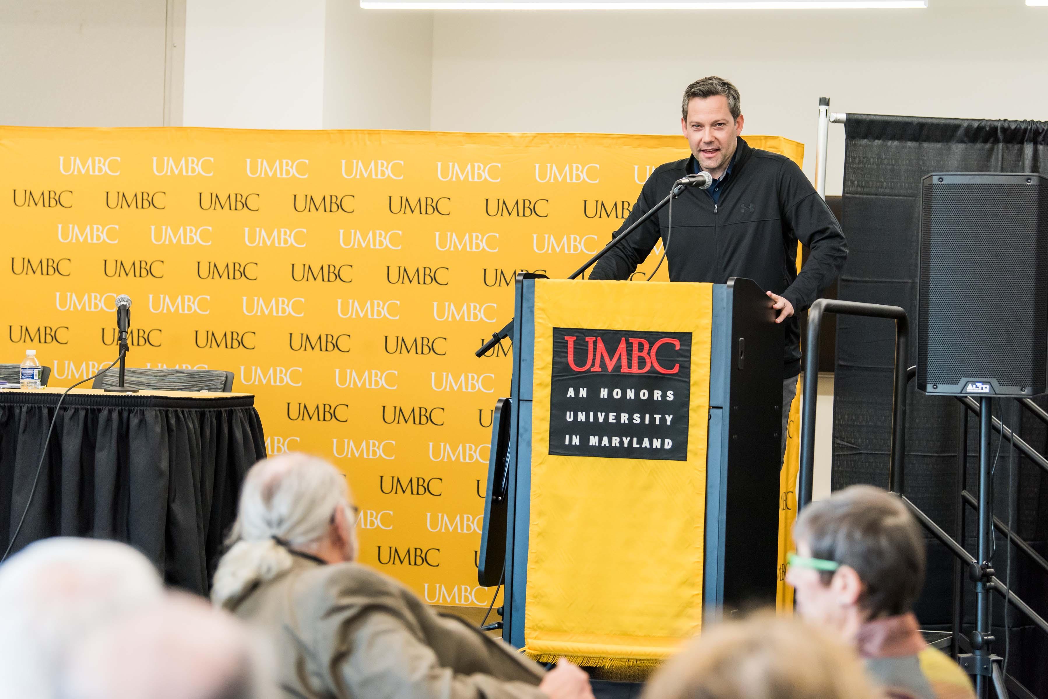 Basketball coach gives speech behind UMBC podium