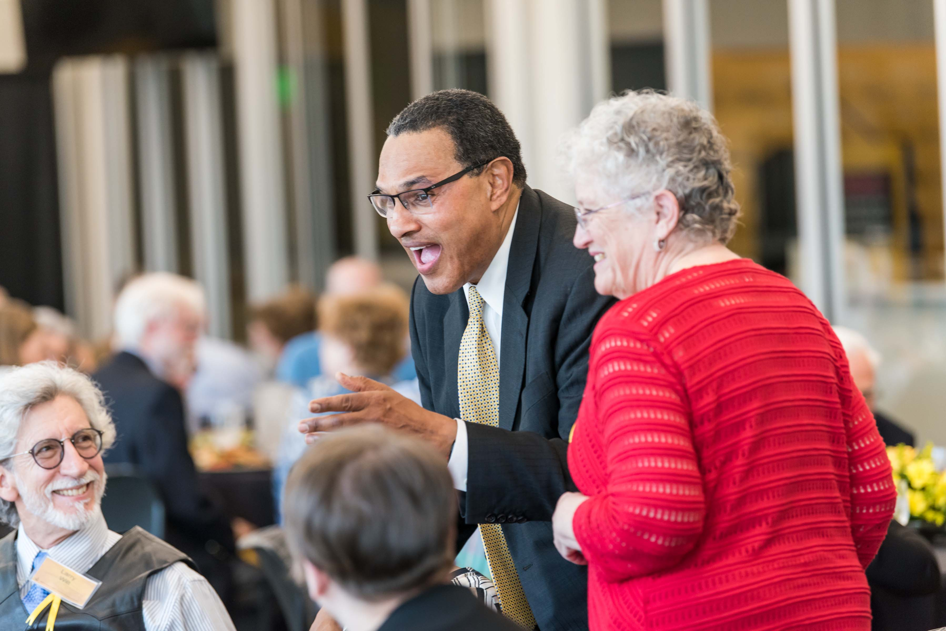 Hrabowski stands and laughs with table at Wisdom Institute lunch