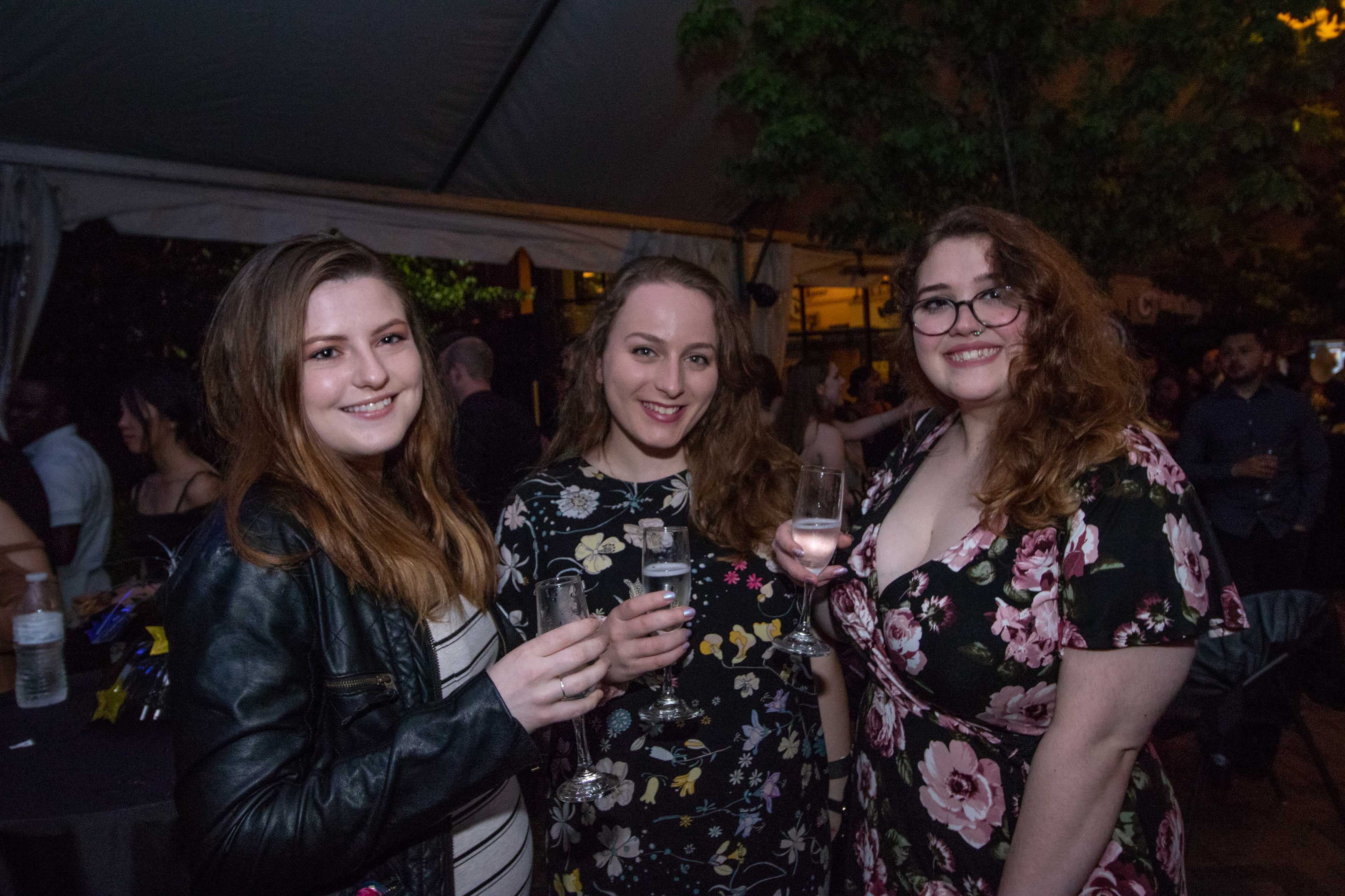 Three girls pose with their wine glasses