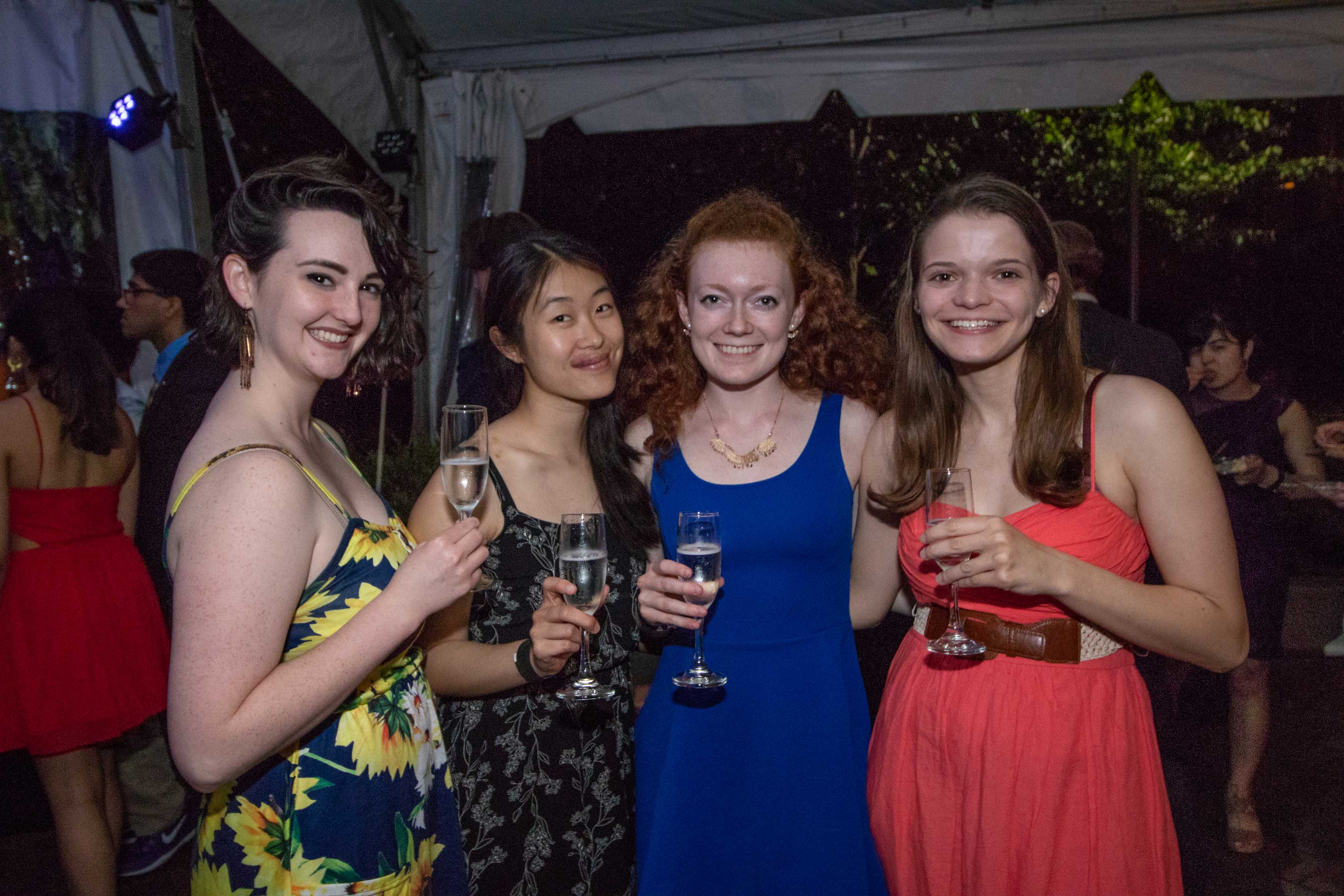 Four women hold up their wine glasses