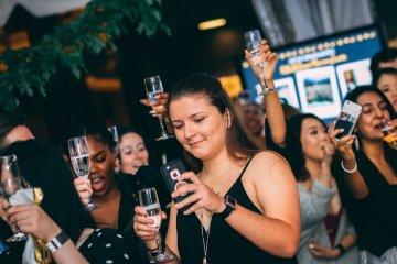 Group hold wine glasses at UMBC grad dance