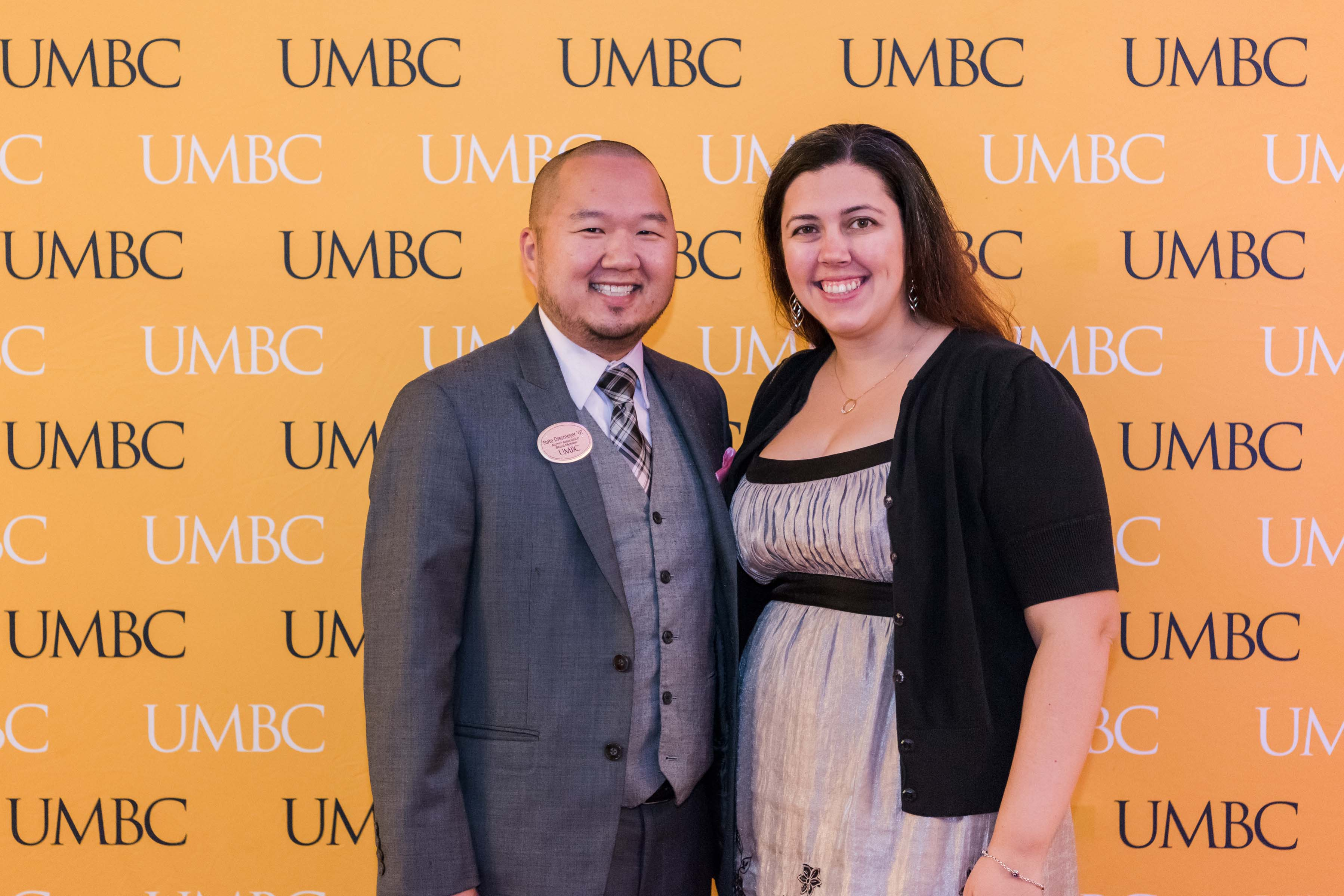 Man and woman pose together at UMBC wall for wine tasting