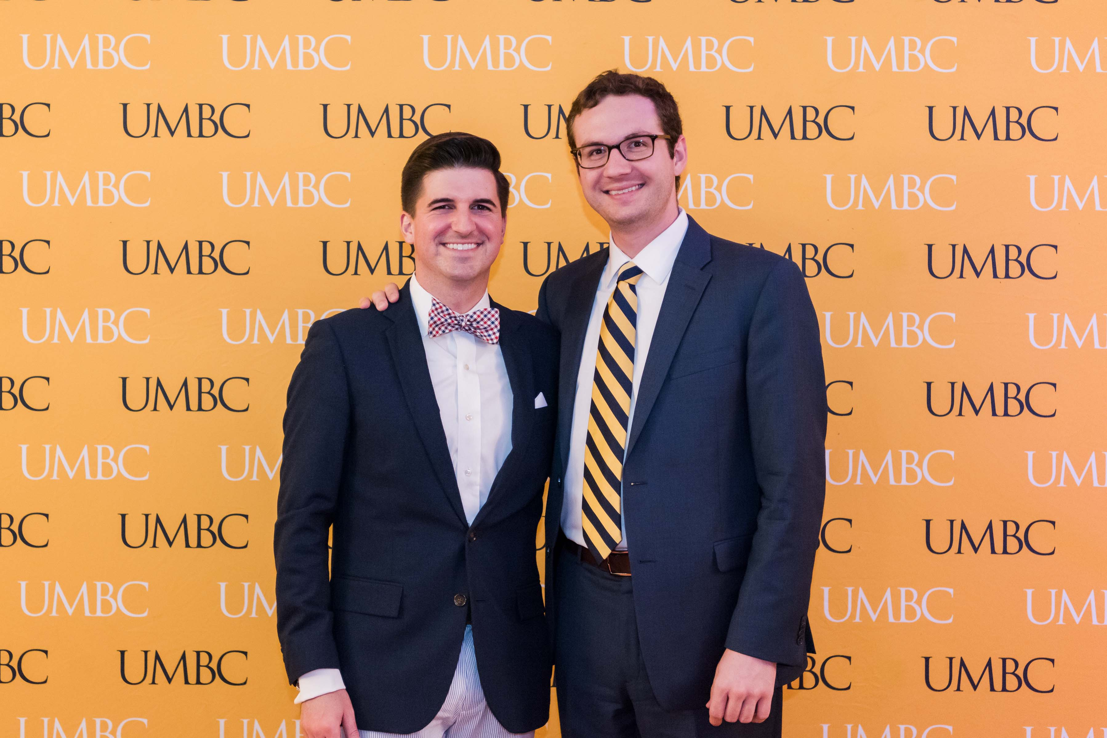 Two guys pose together in front of UMBC wall for wine tasting 2018