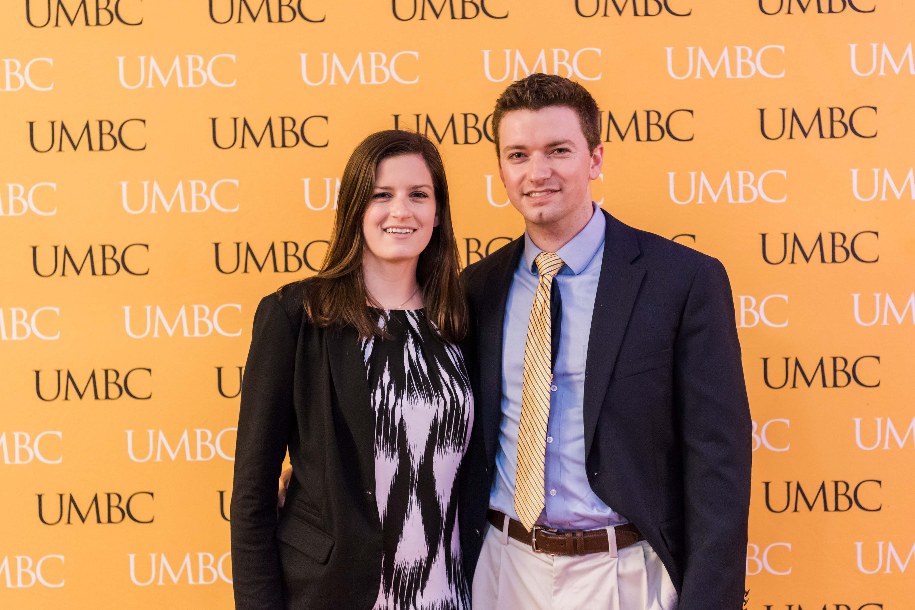 Man and woman pose with UMBC wall