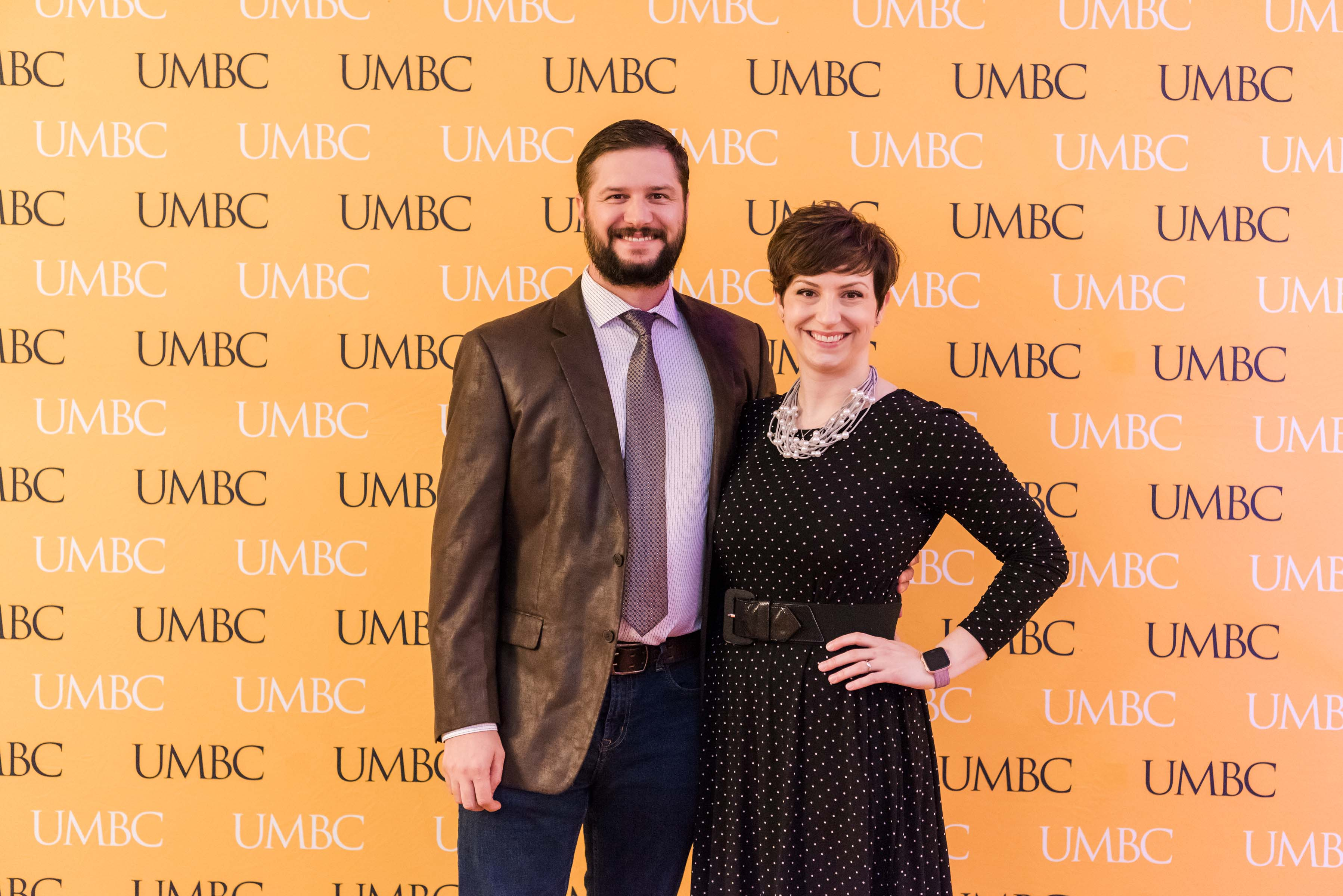 Couple pose at UMBC wall at wine tasting event