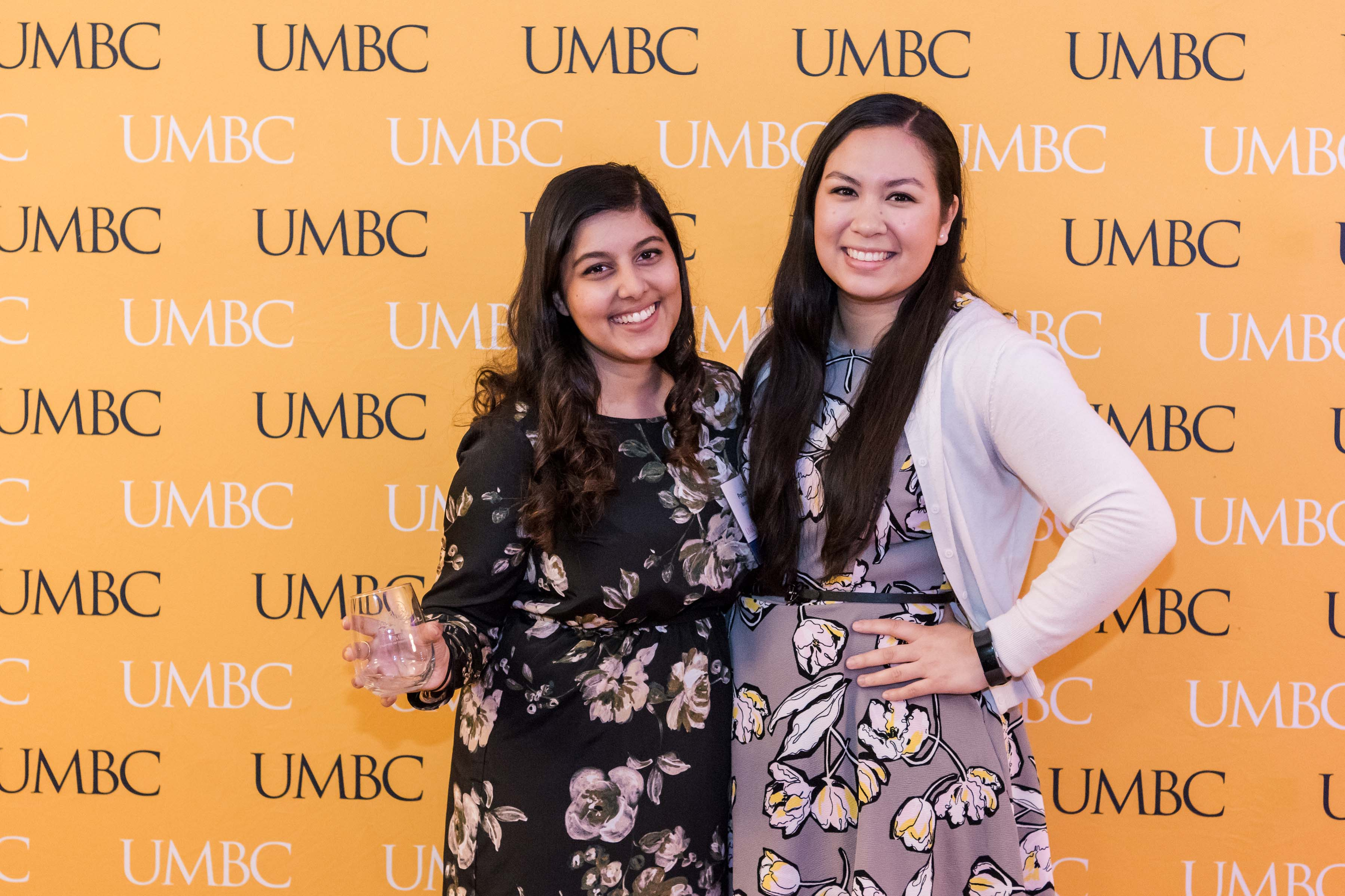 Poulomi poses with woman wine glass in hand at UMBC wall at CYA event