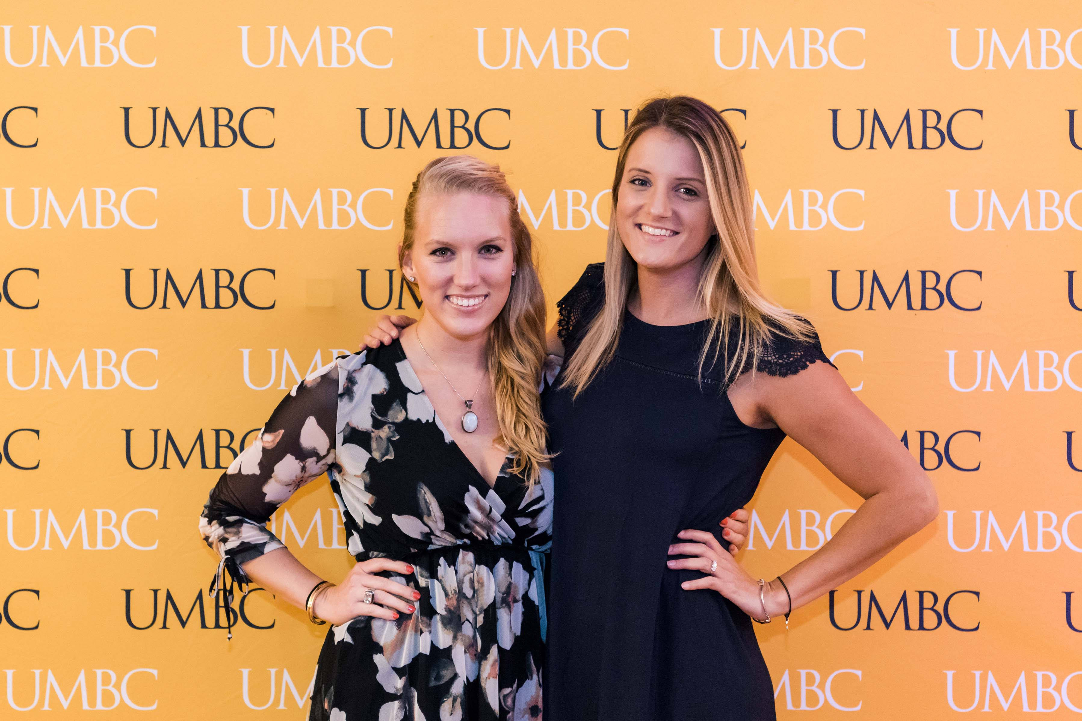 Two women pose together hands on hip at UMBC wall at wine tasting event