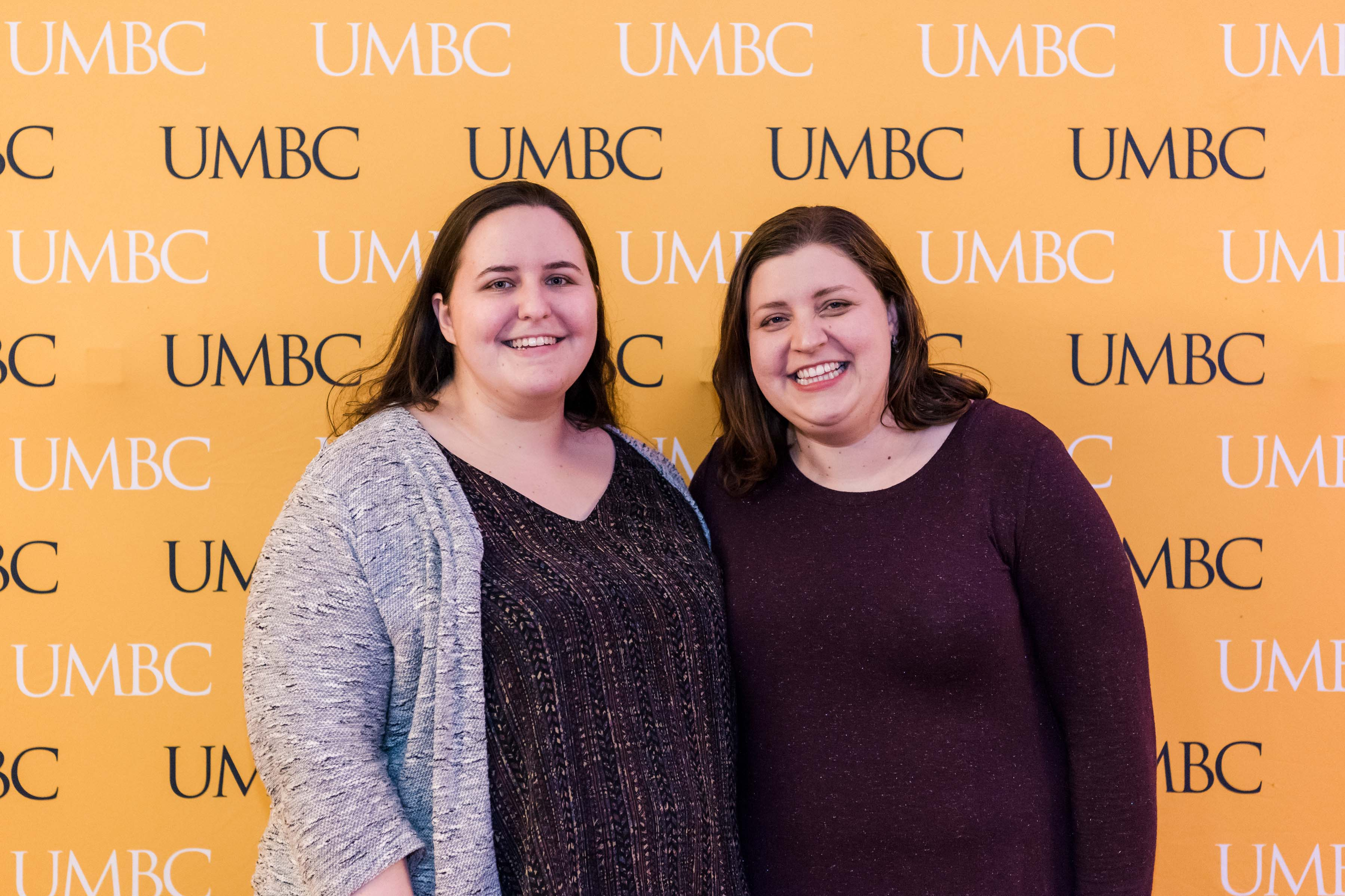 Two women pose at UMBC wall at 2018 wine tasting event