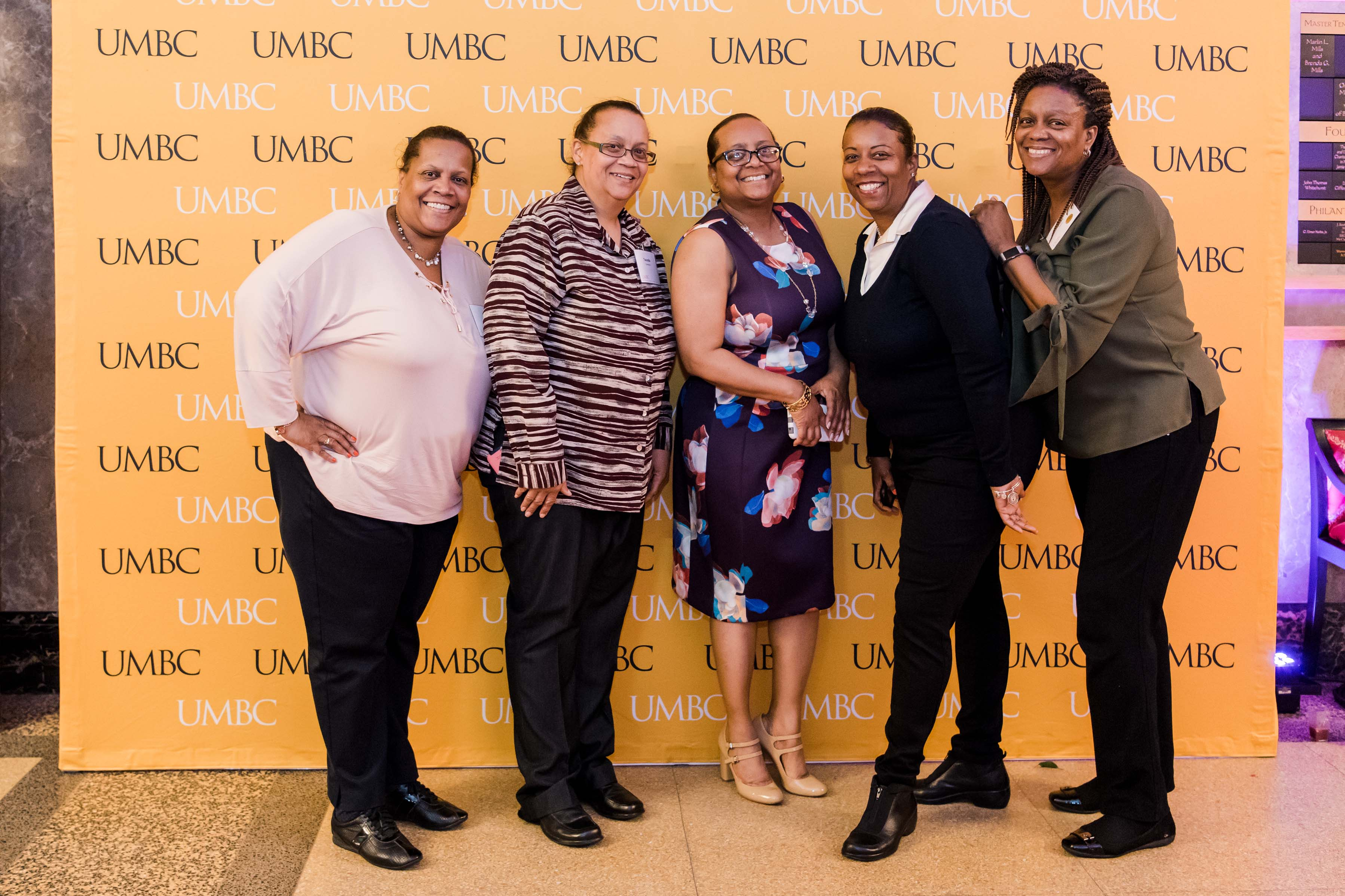 Group of 5 black women pose with UMBC wall at wine tasting event