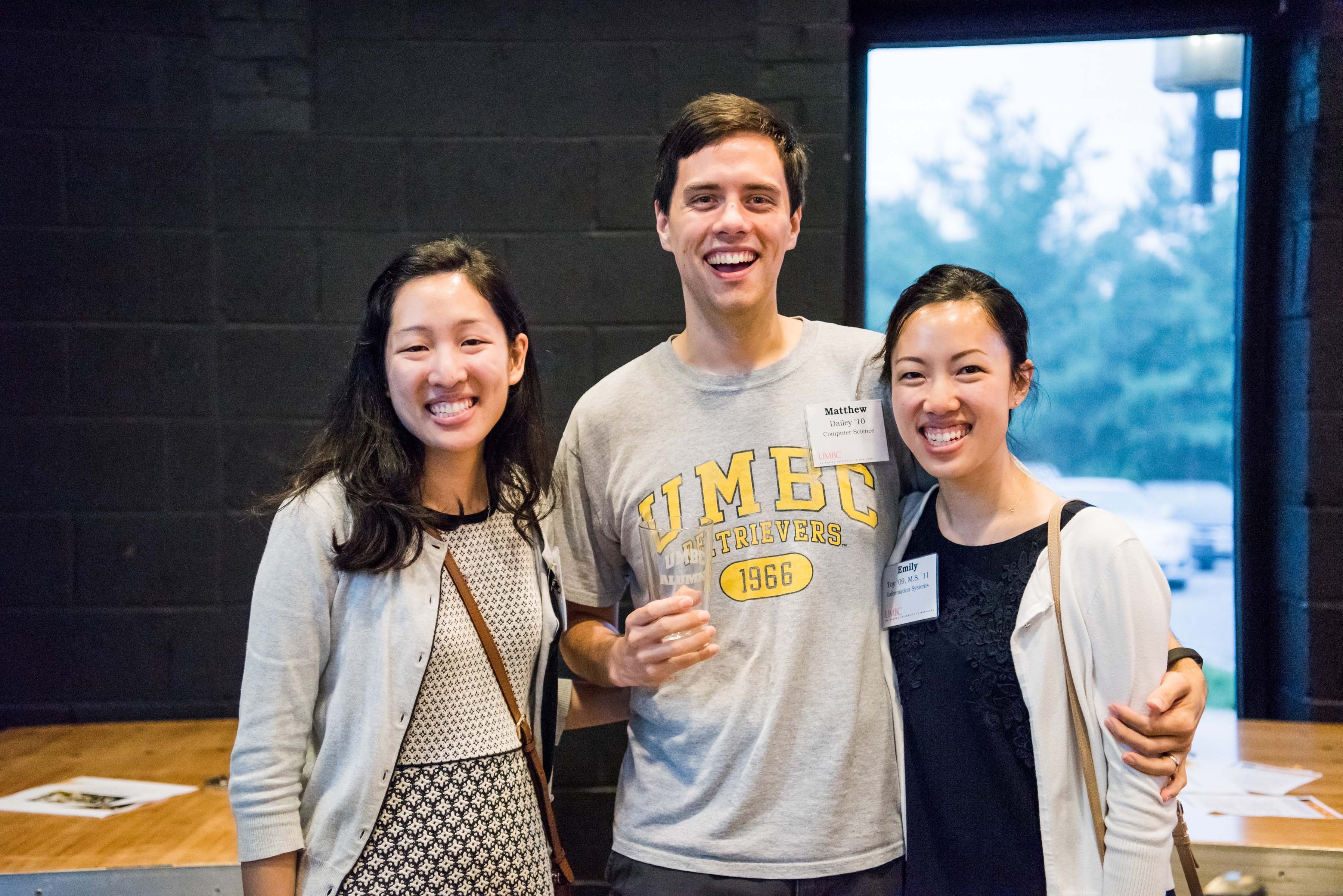 Three people with name tags pose together at Jailbreak Brewing company