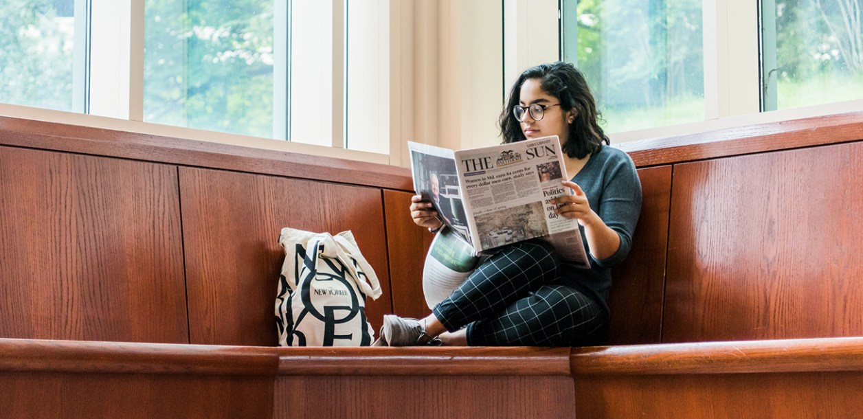 Anjali Dassarma reads the local newspaper at the AOK Library.