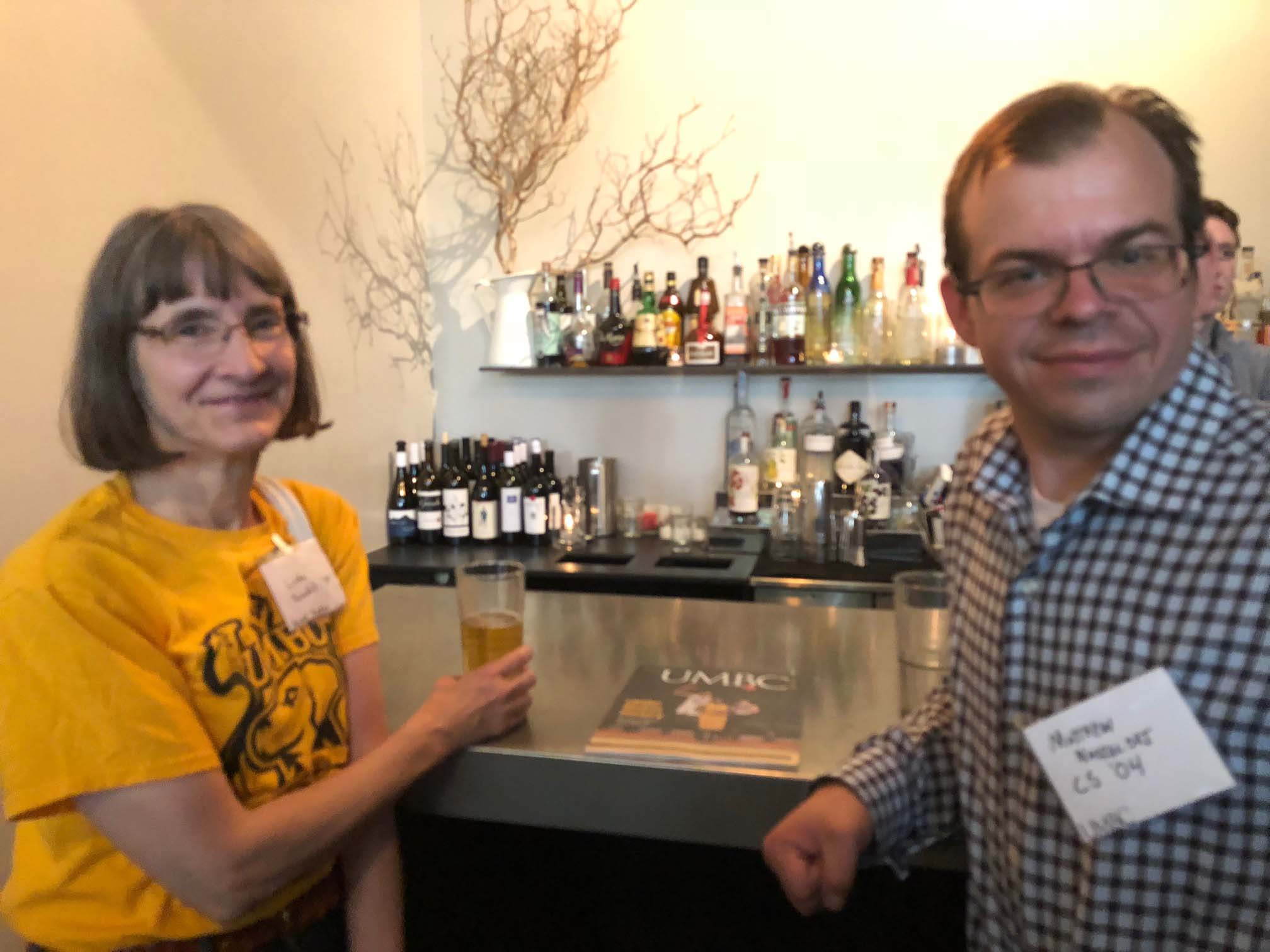 Two people smile at bar at Seattle alumni event