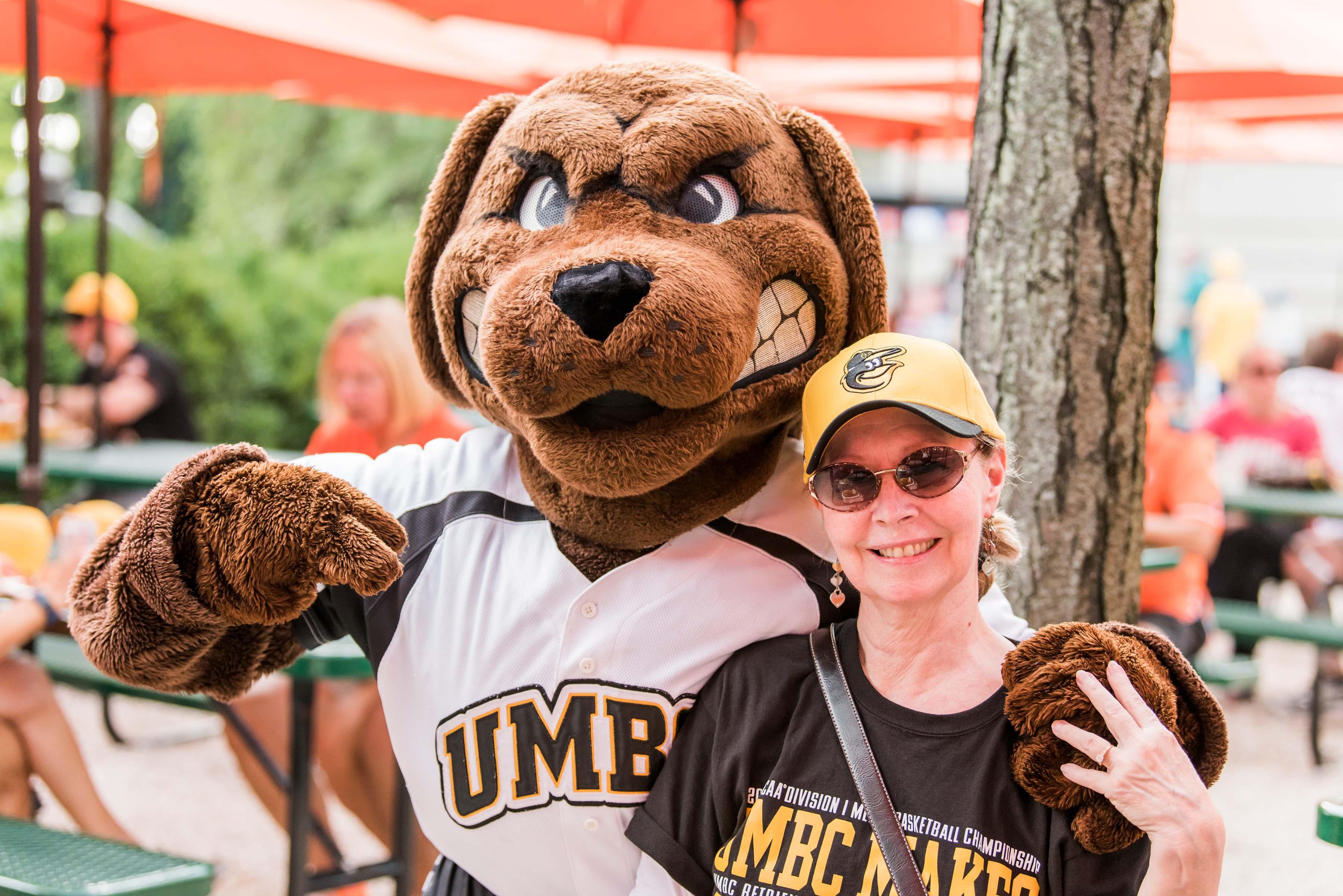 UMBC mascot posing with fan