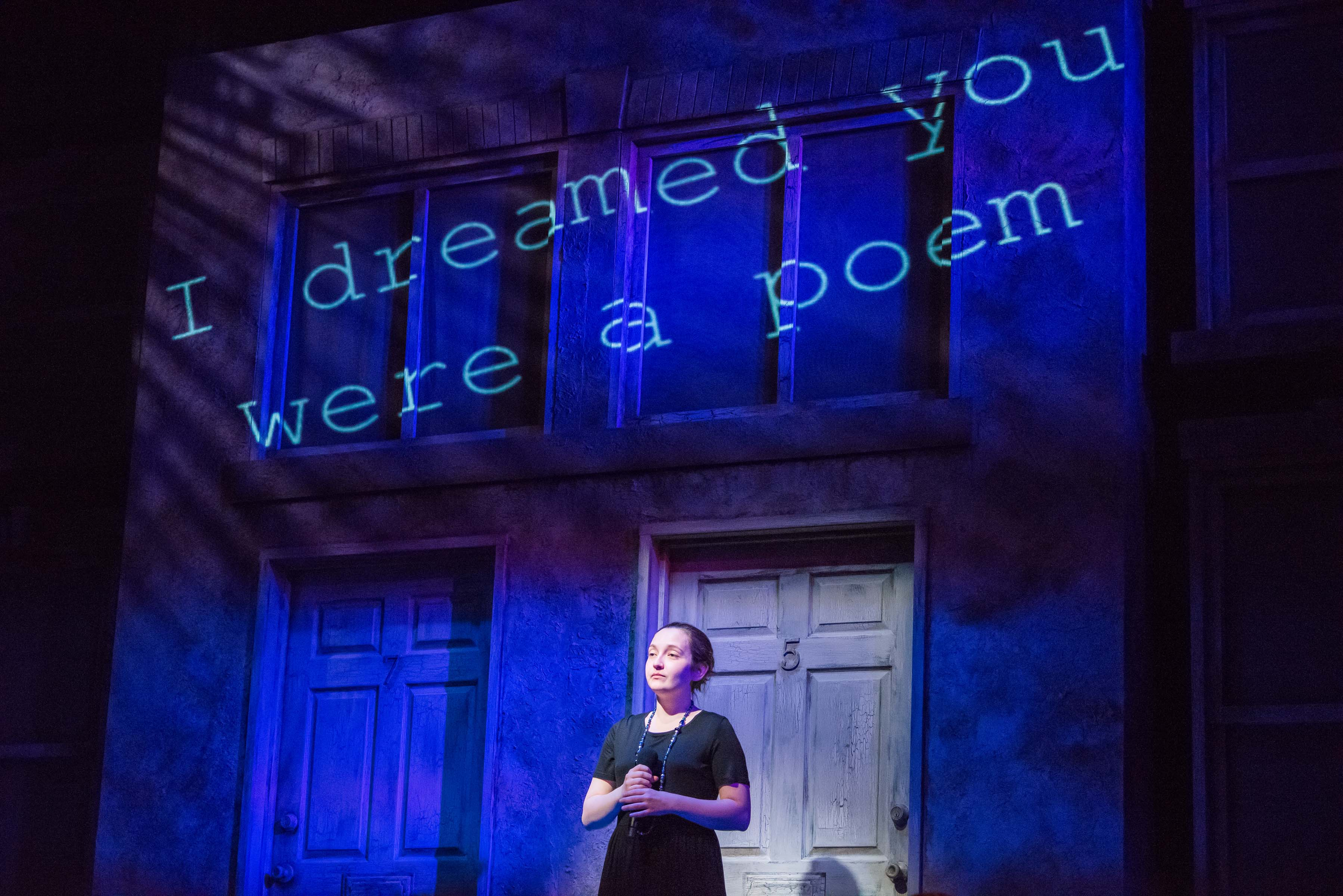 Woman standing with microphone on stage I dreamed you were a poem lit up behind her