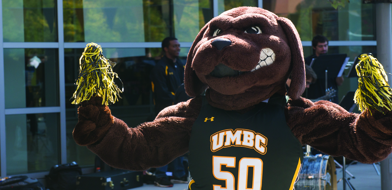 True grit mascot with pom poms the umbc band behind him