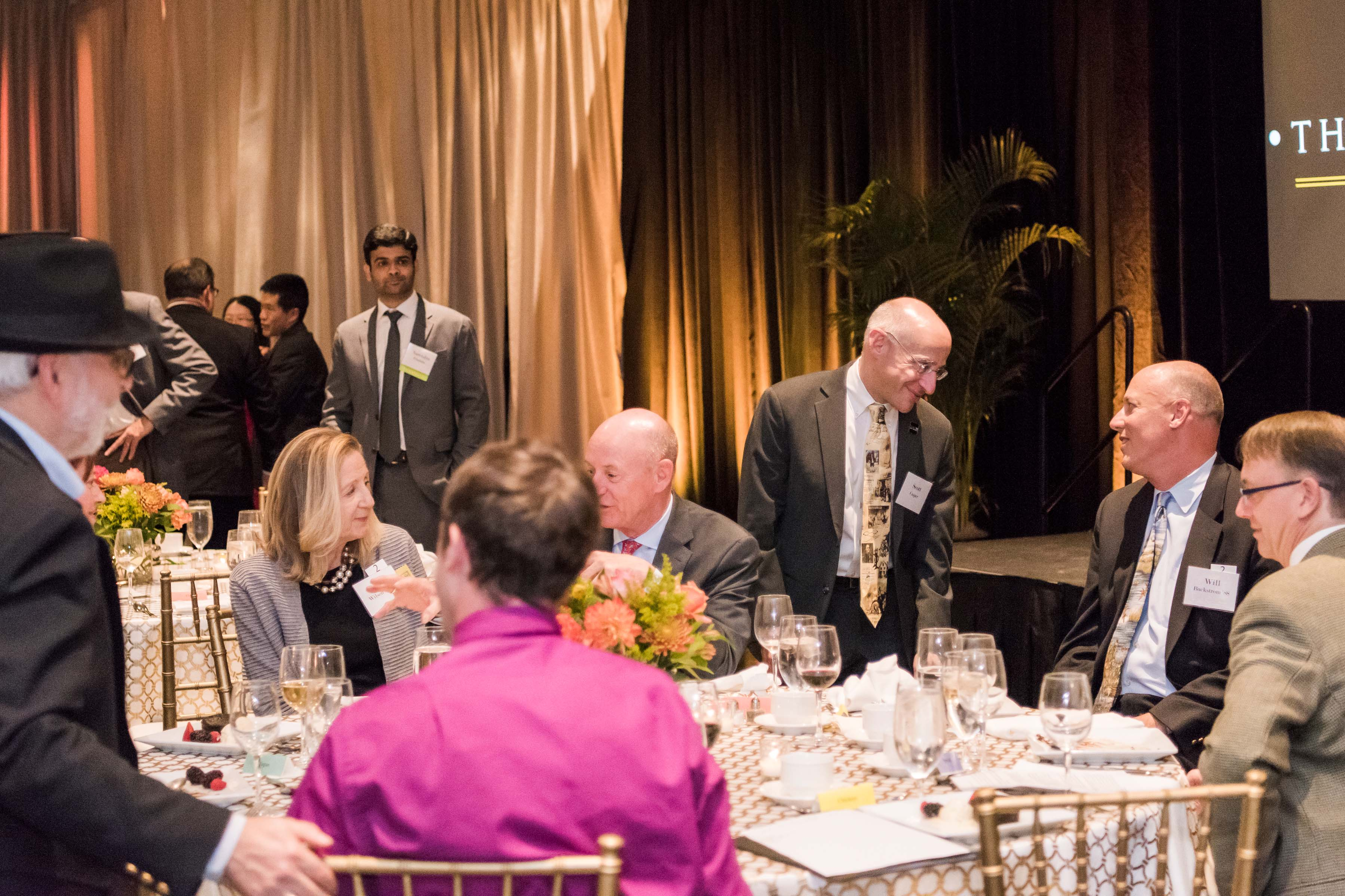 Guests talk around tables after dinner
