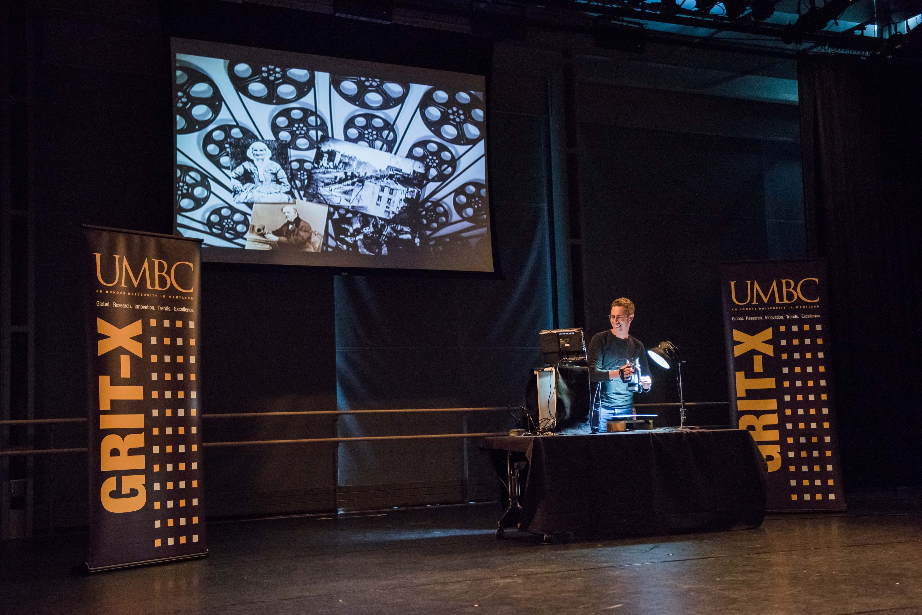 Man presents with visual aids and presentation at Grit X