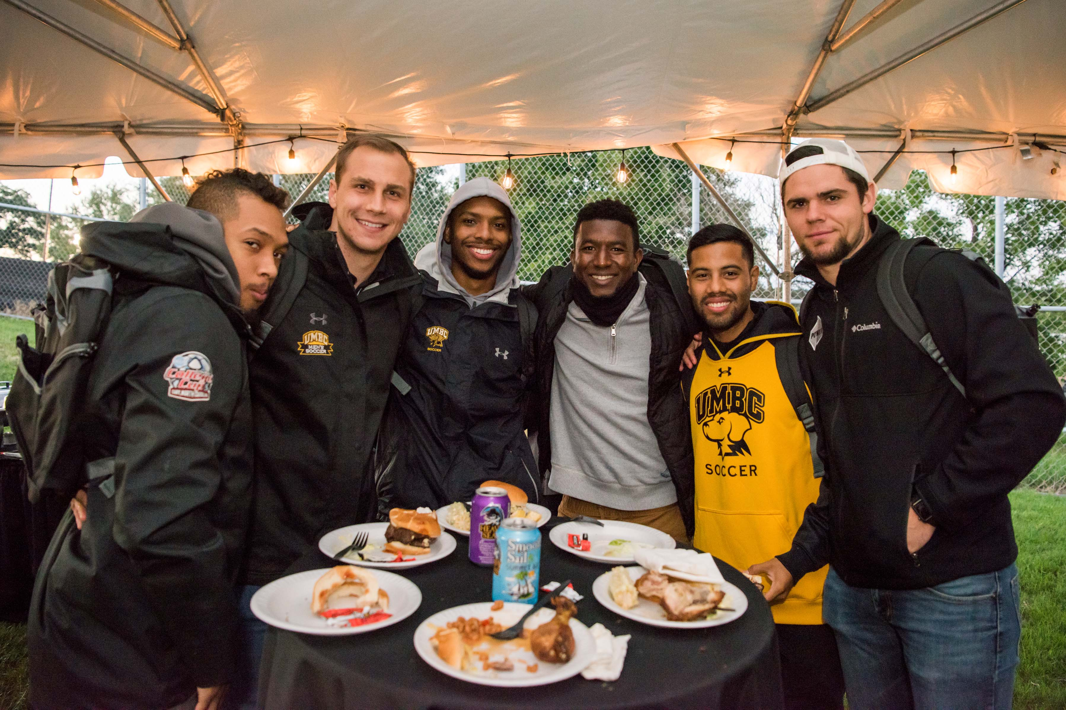 Group of guys pose behind black circular table with food on it