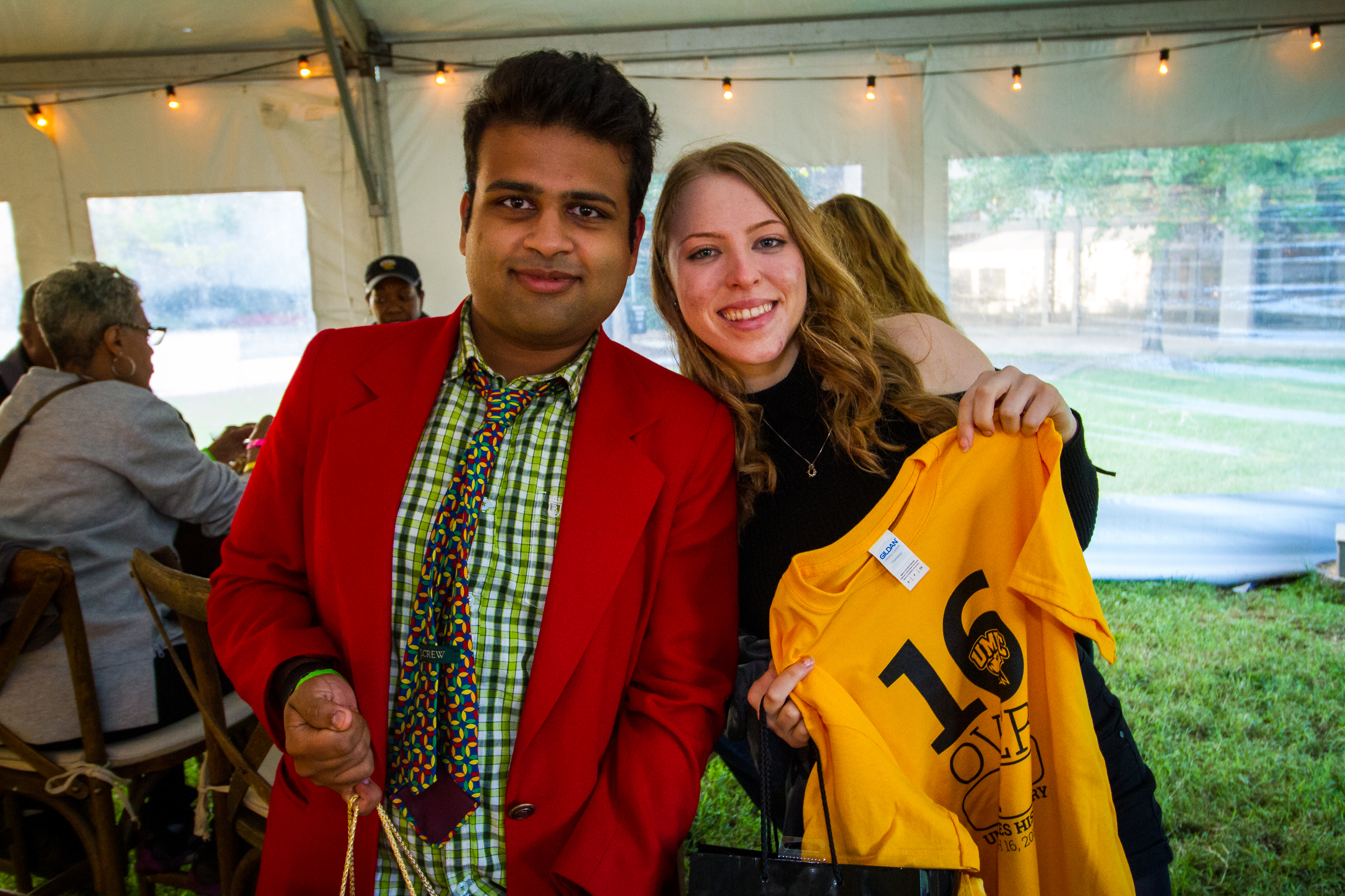 Man and woman pose together at Homecoming Woman holding 16 over UMBC shirt