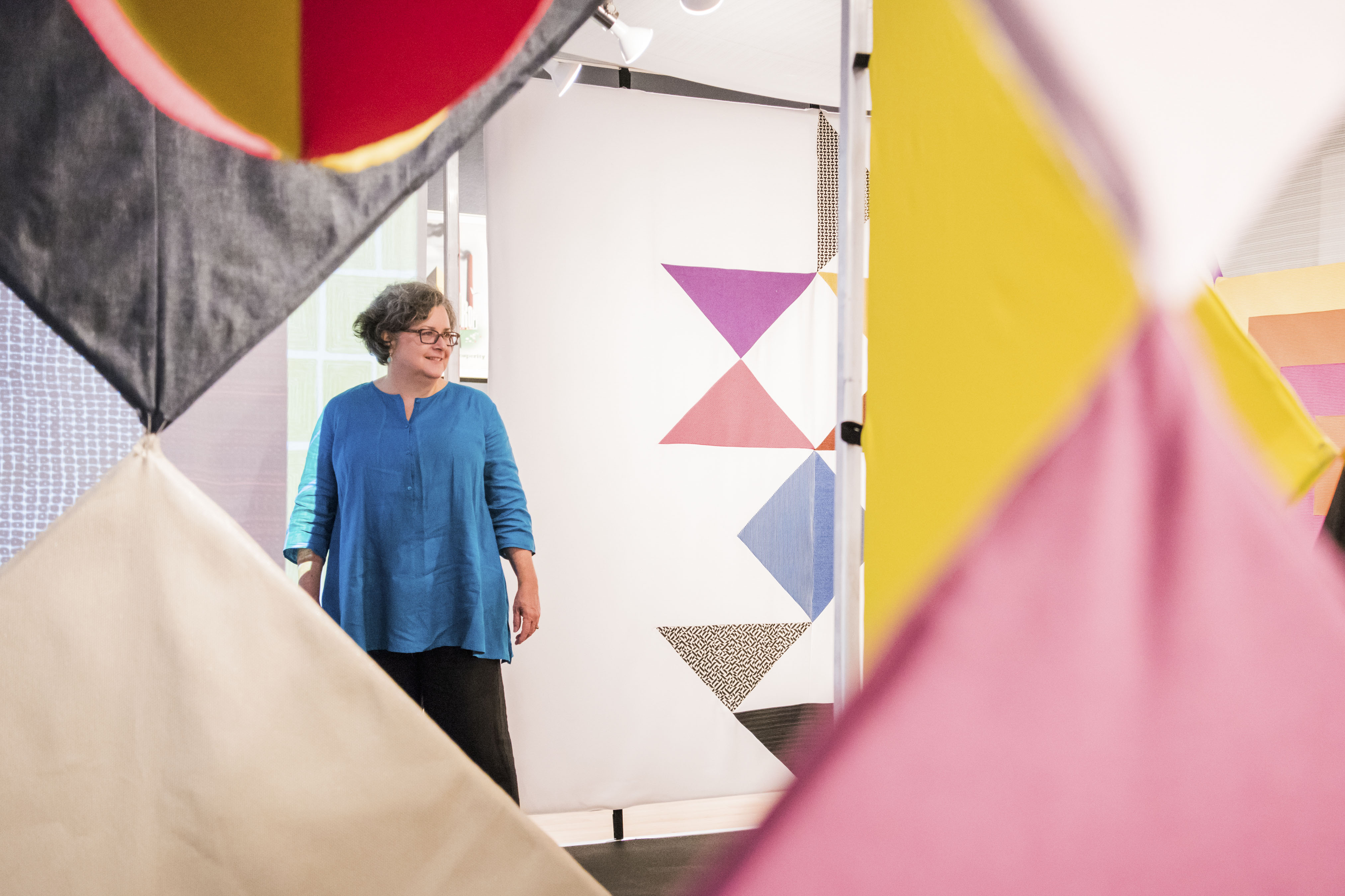 Woman framed by fabric from art exhibit