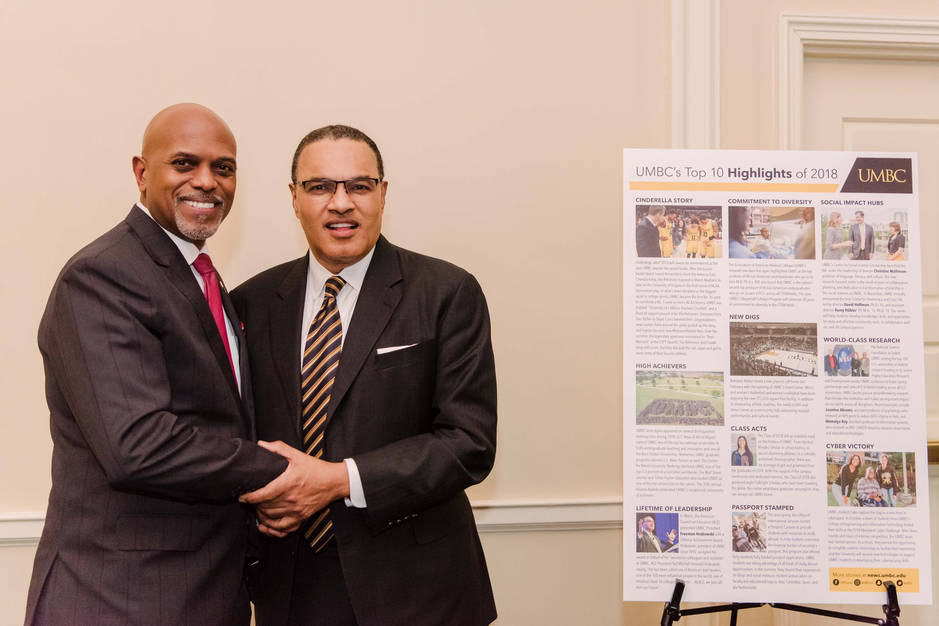 Hrabowski and other man shake hands and smile at camera UMBC's top 10 highlights sign in background