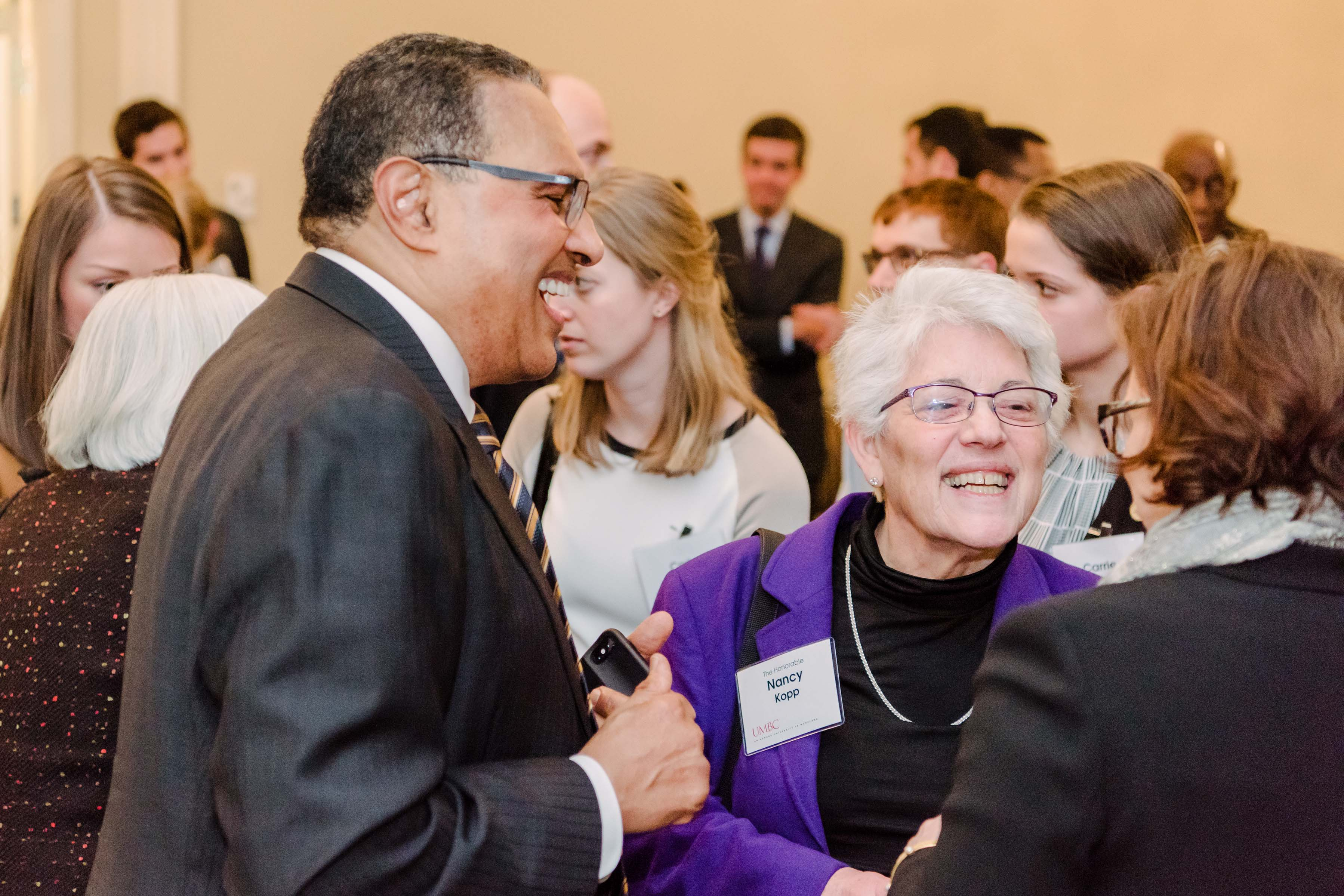 Hrabowski laughs with group of women at Annapolis alumni reception
