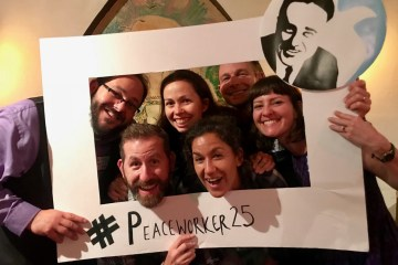 Six people pose inside #Peaceworker25 frame