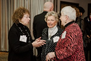 Three women stand in circle talking at scholarship luncheon