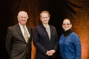 Woman poses between smiling couple and scholarship luncheon