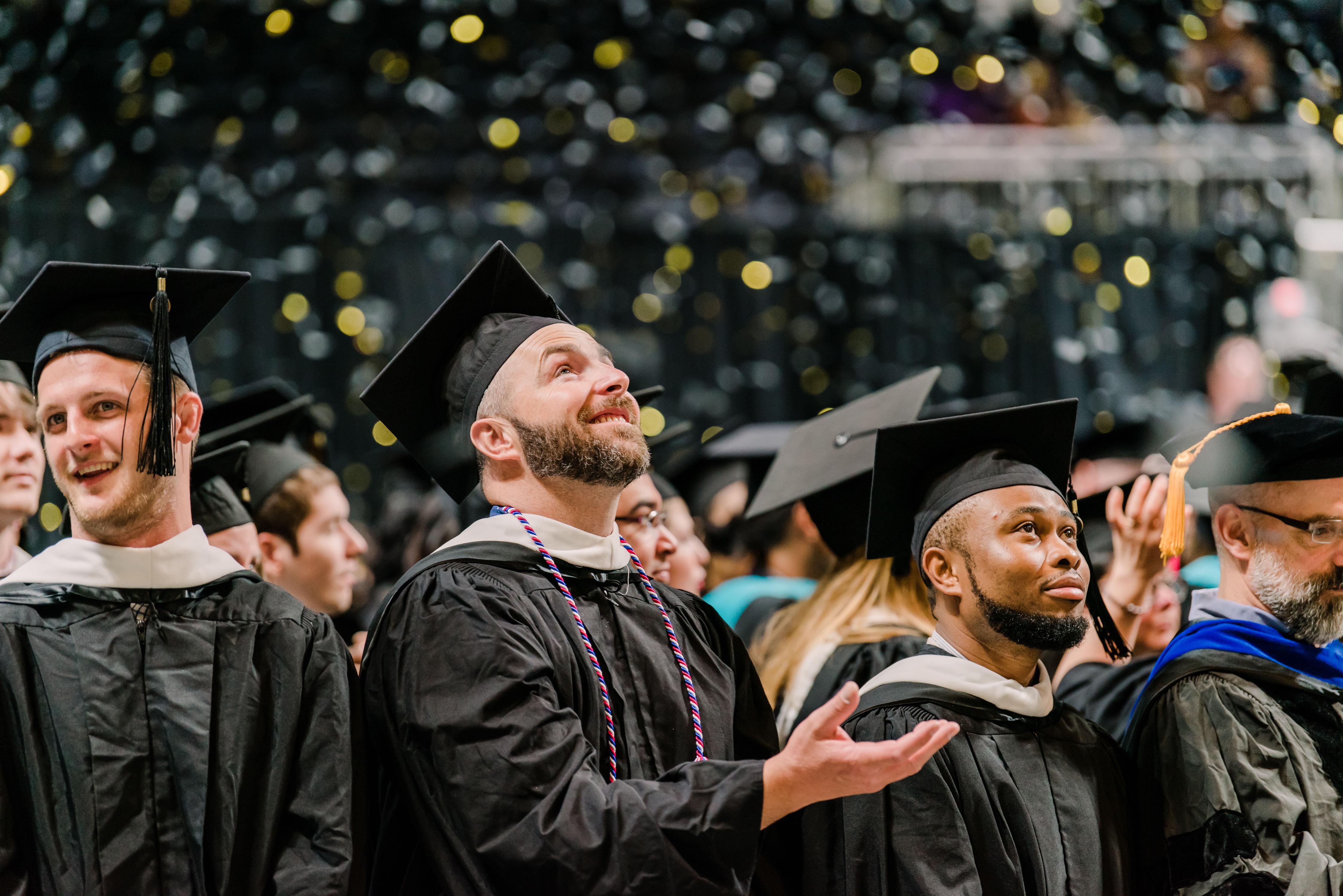 Graduate smiles up at confetti at graduation