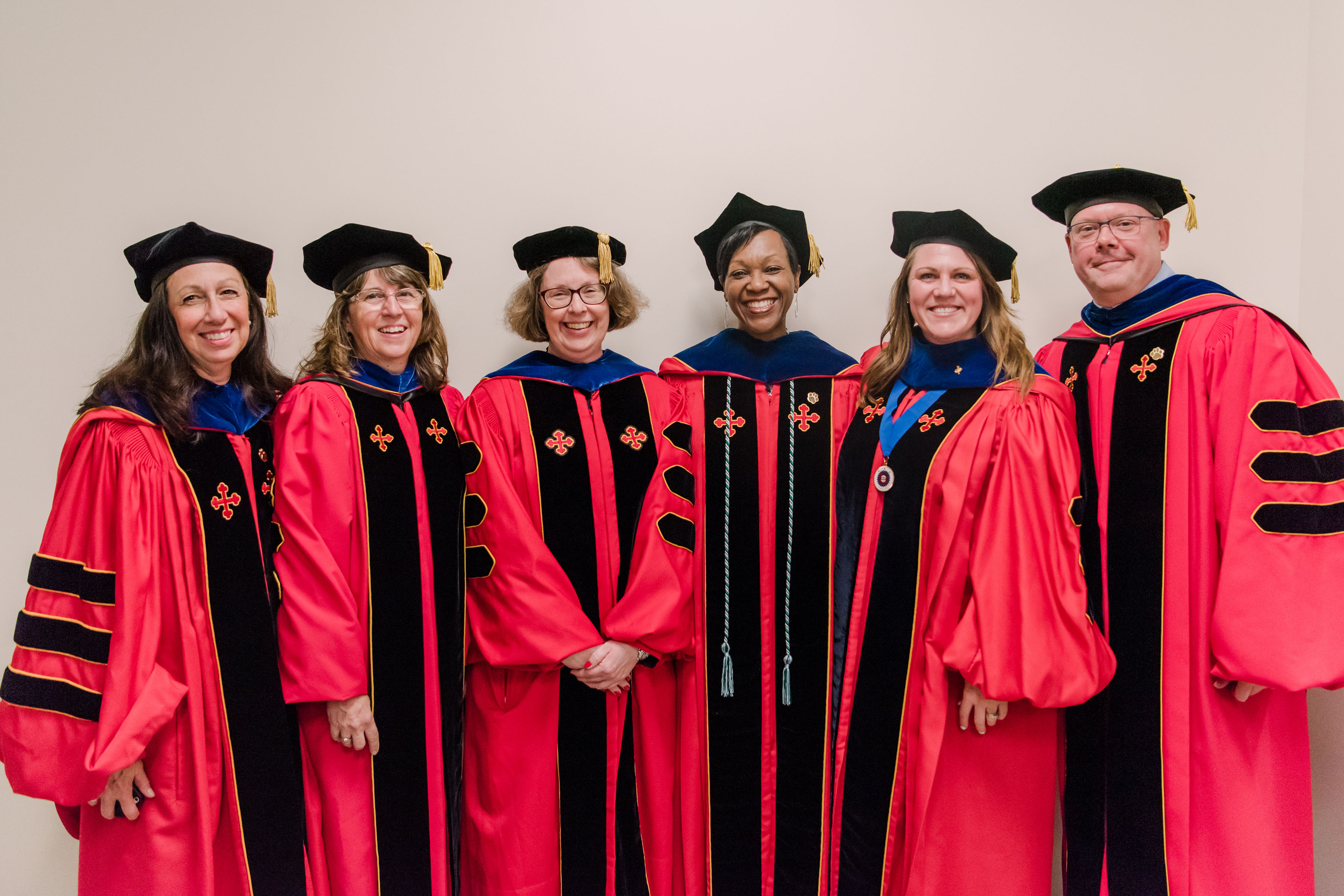 VP Nancy young and others pose and smile together in red graduation regalia