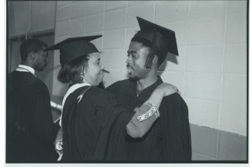 Woman and man embrace with graduation regalia in black and white picture