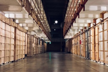 a hallway in between prison cells