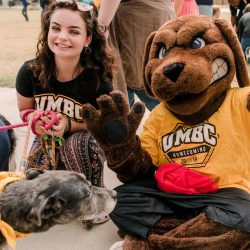 UMBC mascot poses with students and dogs