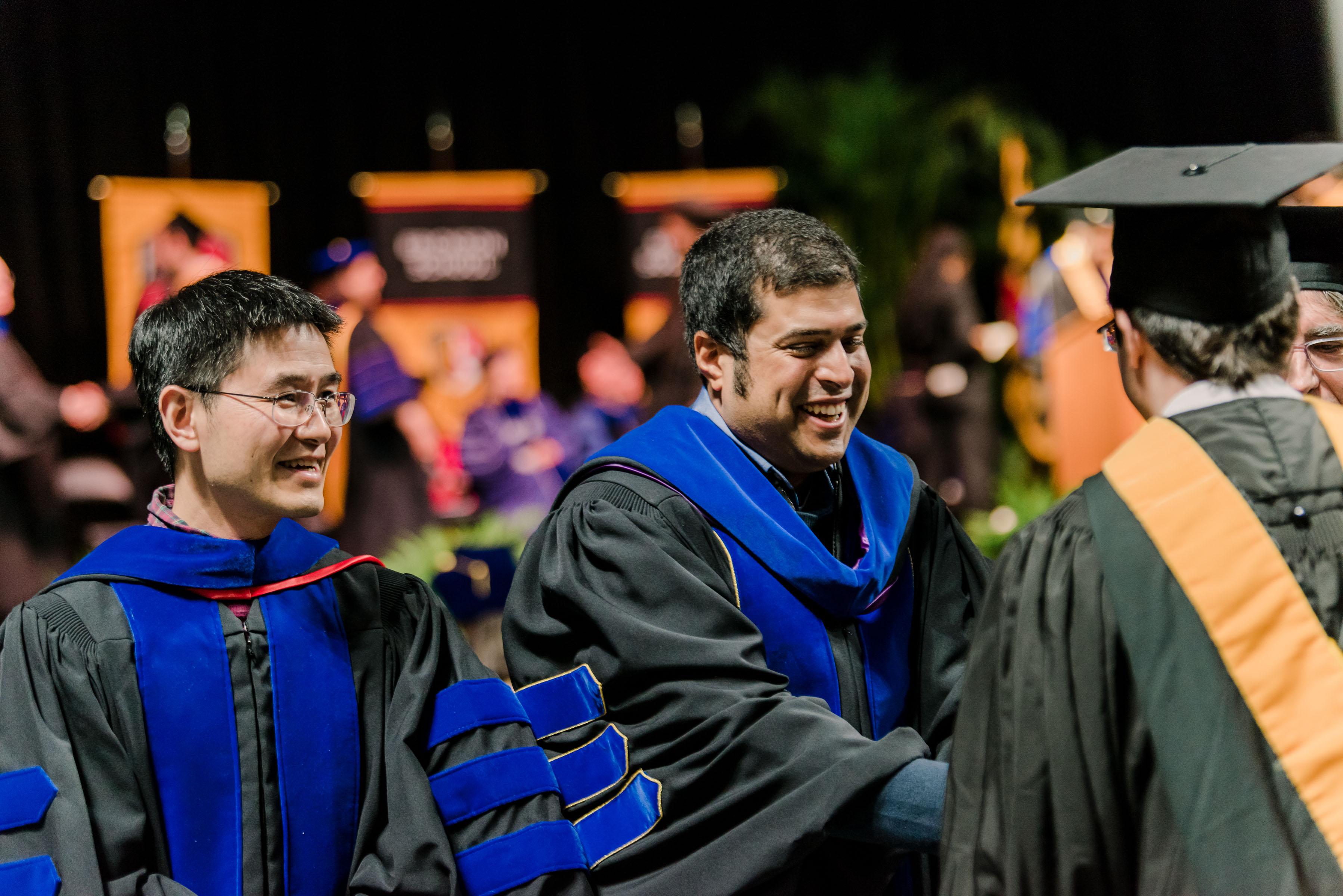 professors in graduation garb interact