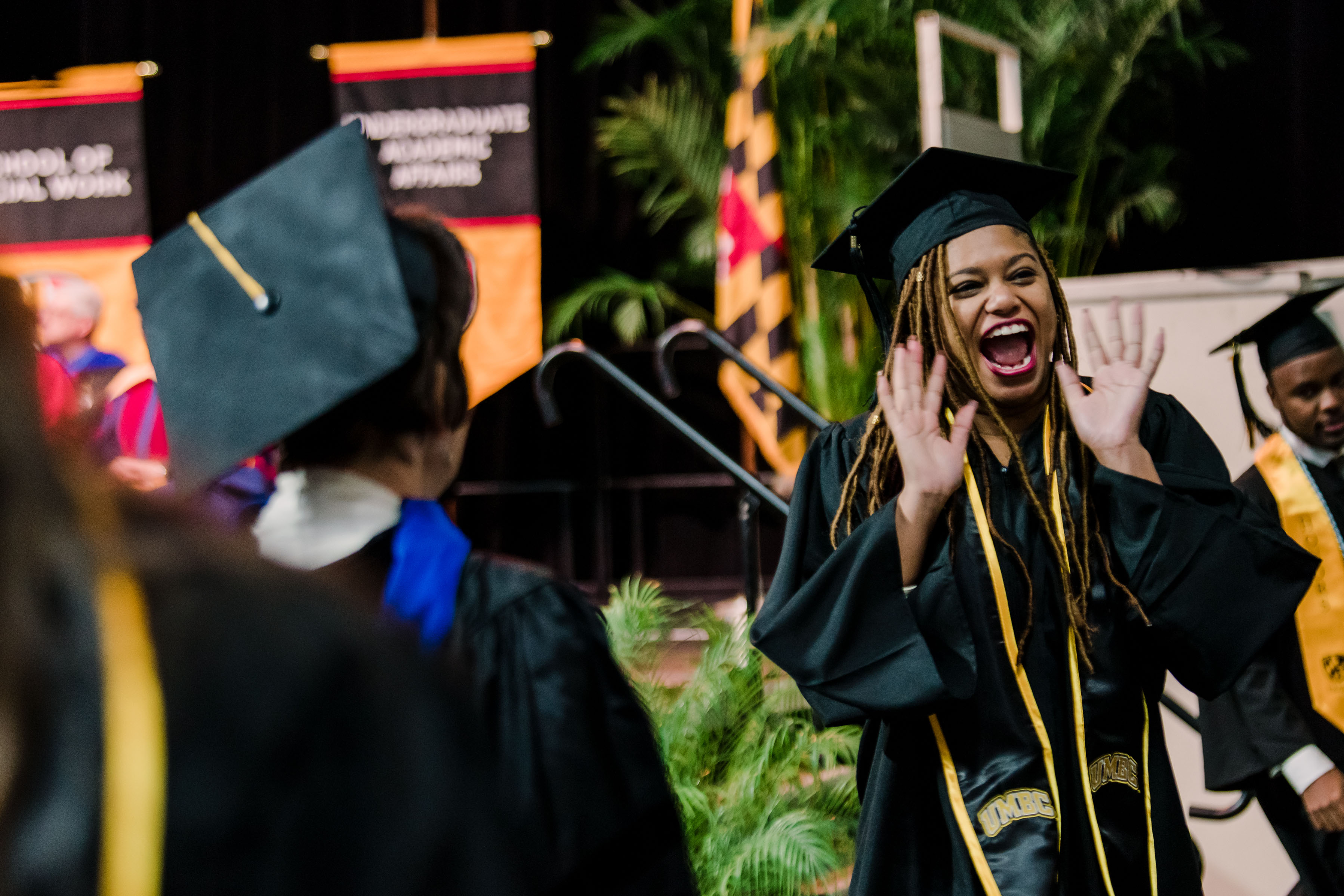 woman celebrates in graduation robes