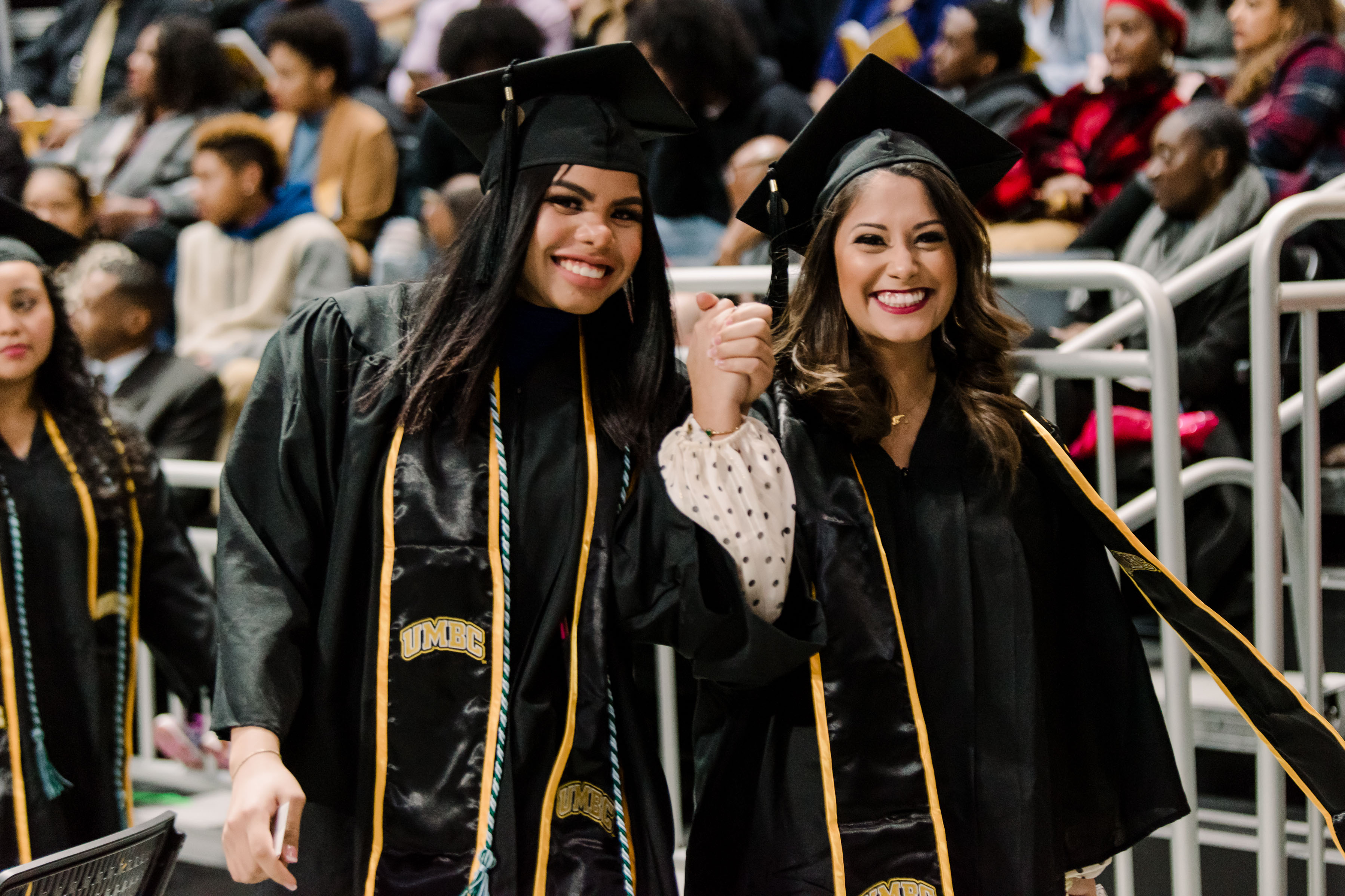 graduating girls hold hands and smile