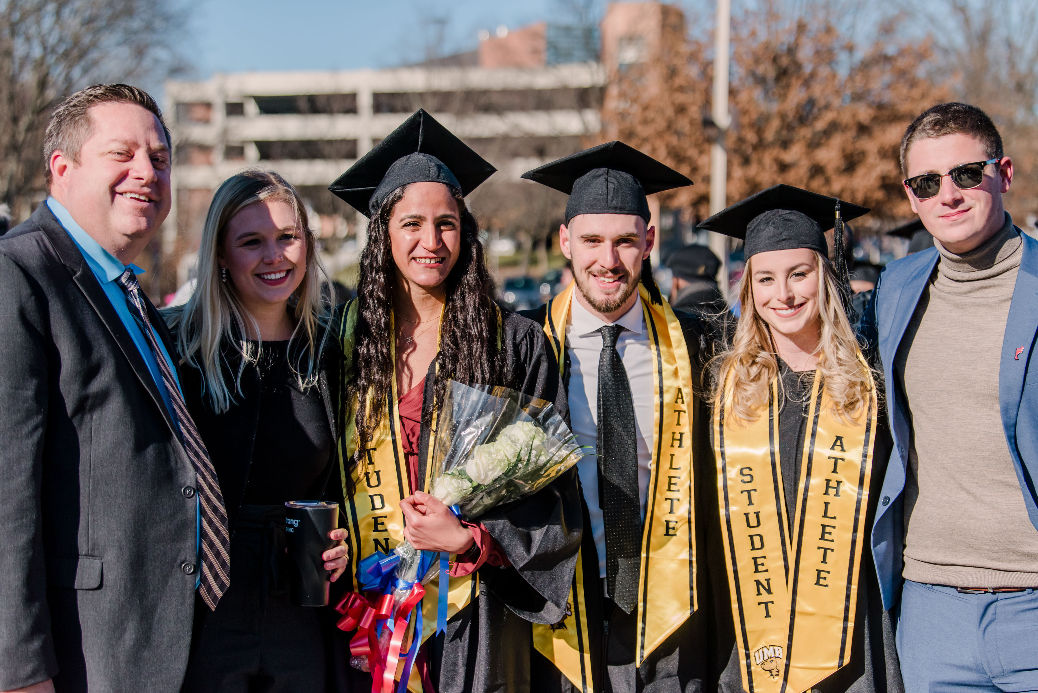 athletic graduate students pose with flowers and others