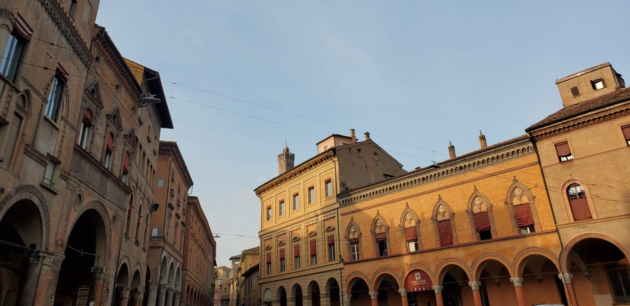 The sun shines on a long building in Bologna, Italy.