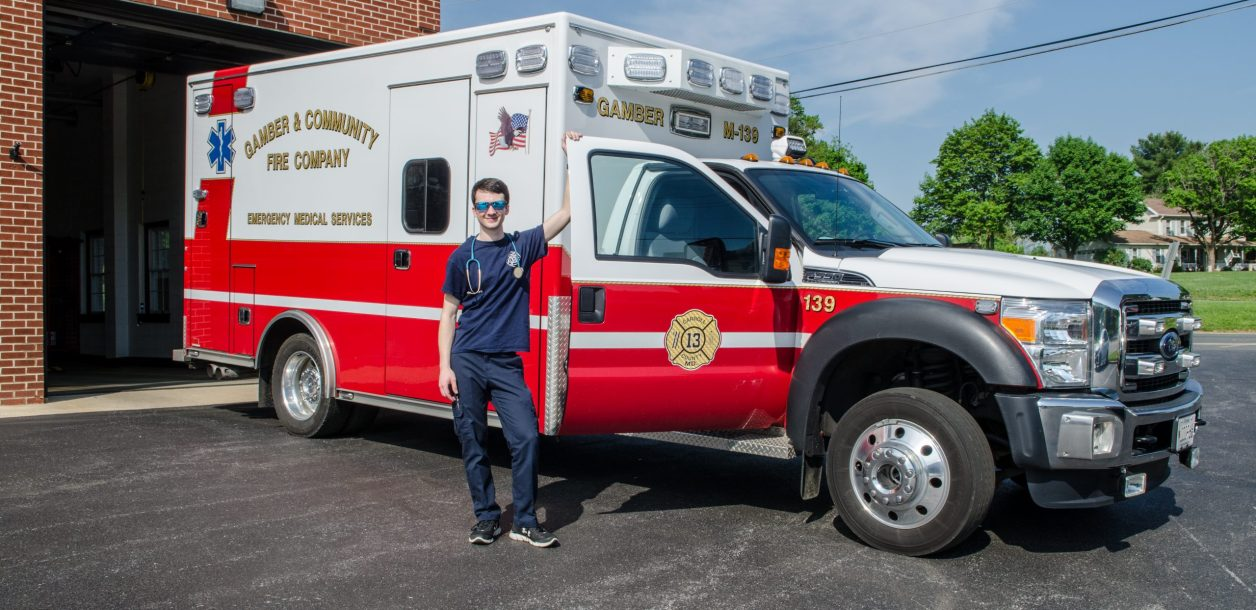 Jack Bez stands in front of a Gamber and Community Fire and Company ambulance with a stethoscope on