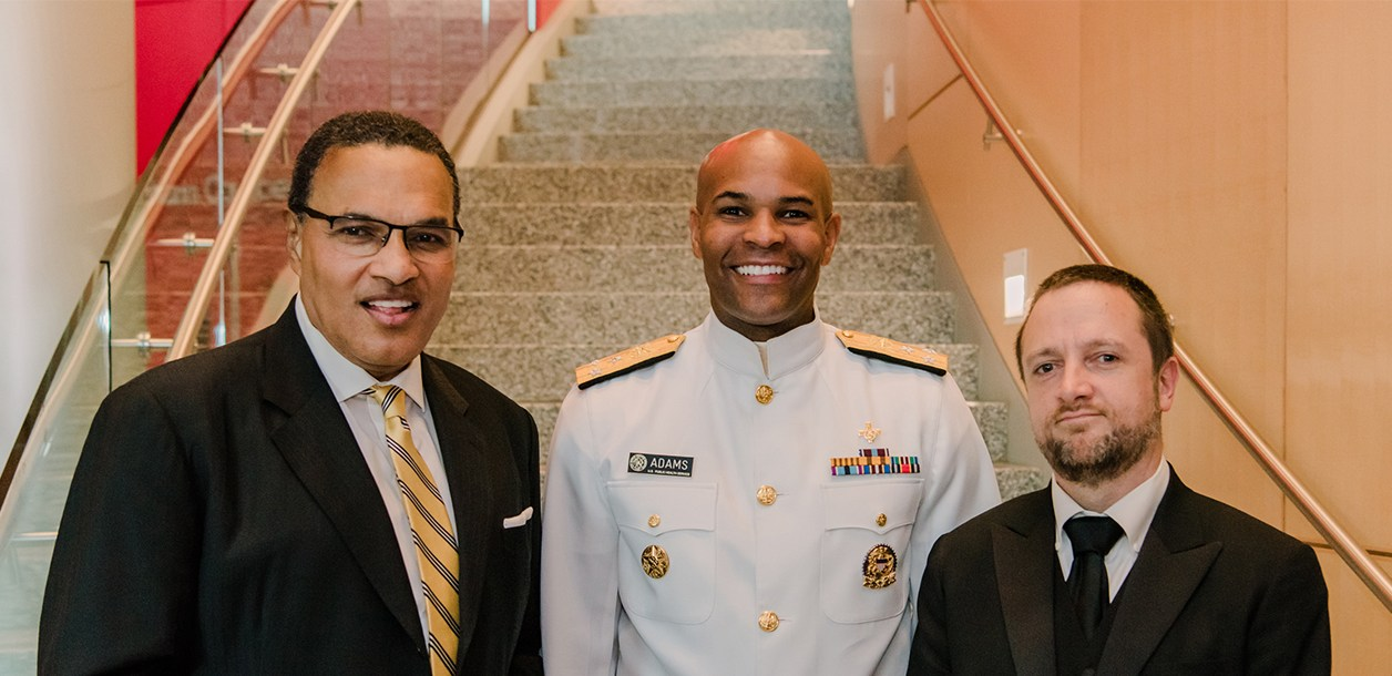 Surgeon General of the United States Jerome Adams stands in the middle of UMBC President Dr. Freeman Hrabowski and John Becker