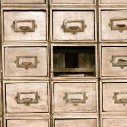 Sepia-toned wall of mail drawers with the center drawer missing