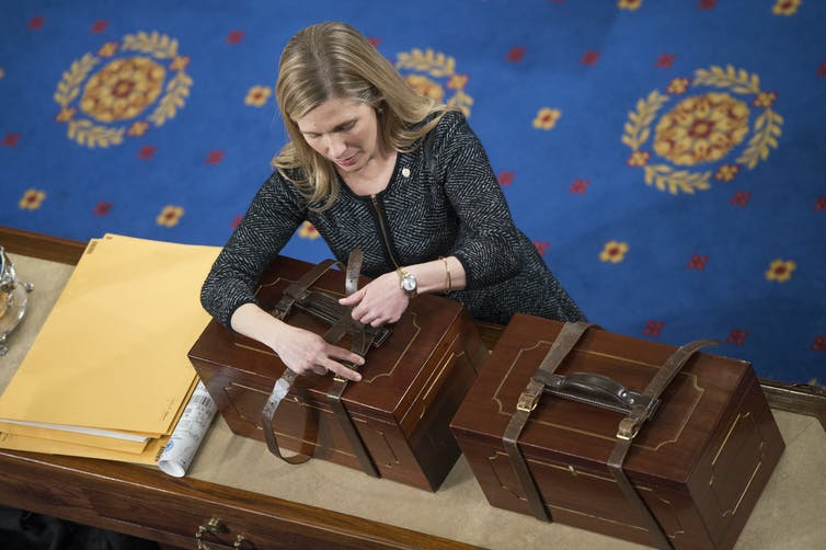 A congressional staffer in a dress opens a a box containing Electoral College ballots