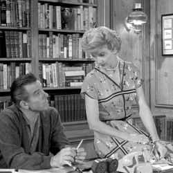 """Scene from sitcom """"Leave It to Beaver"""" showing Beaver and his wife in his study"""